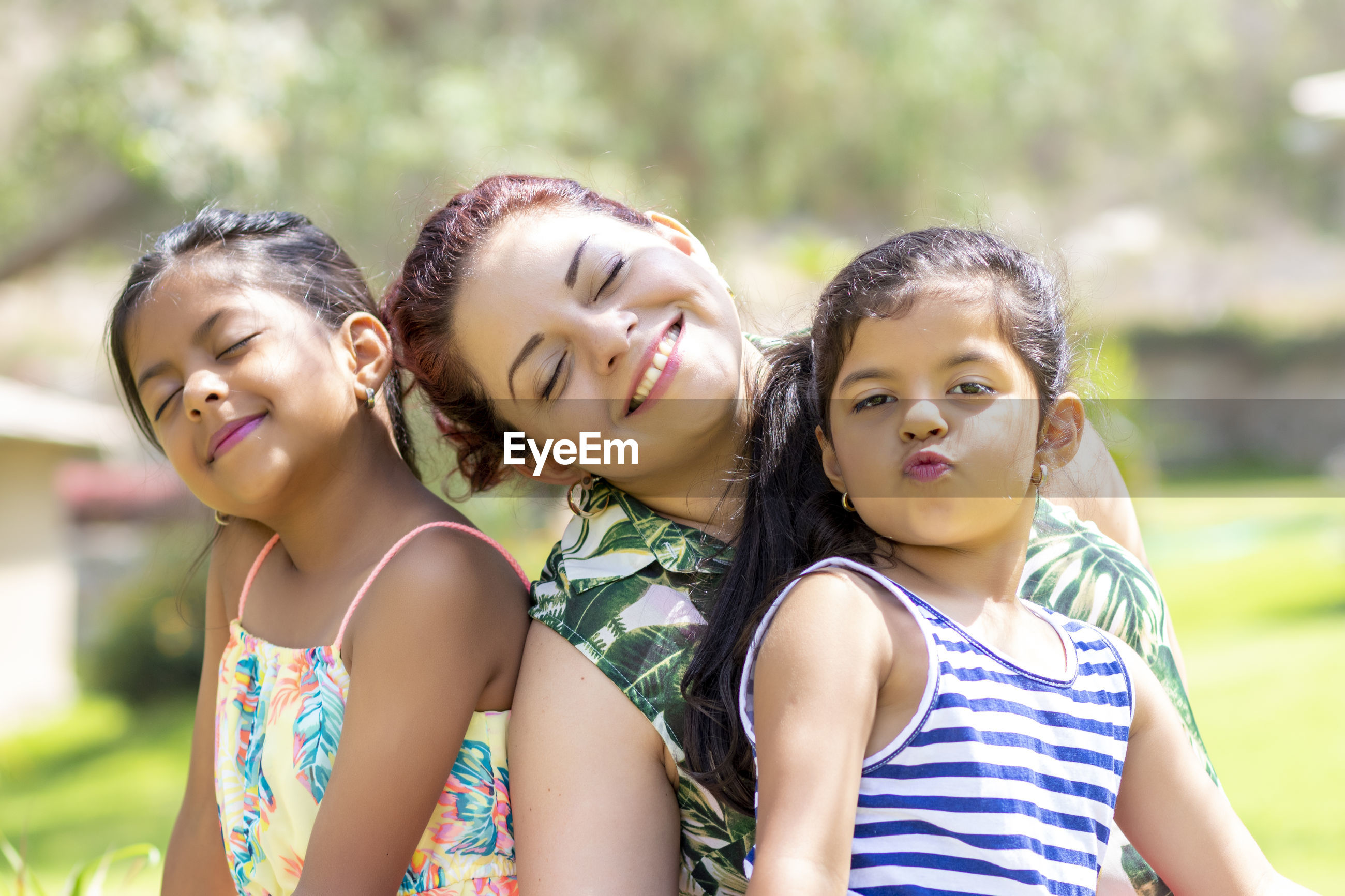 Smiling woman with daughters sitting in backyard