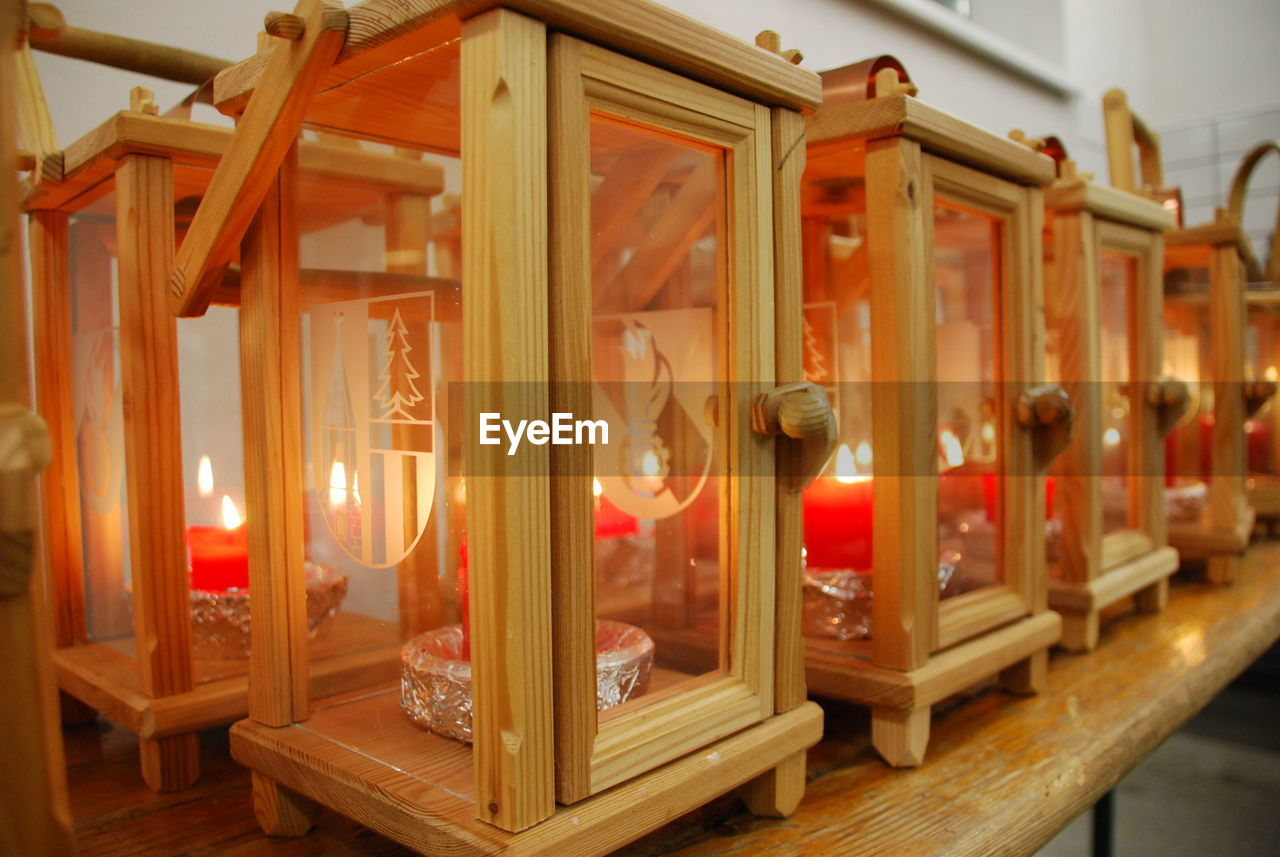 wood - material, candle, illuminated, indoors, no people, lighting equipment, flame, architecture, in a row, burning, heat - temperature, fire, built structure, building, glowing, glass - material, large group of objects, shelf, home interior, focus on foreground, ceiling, tea light