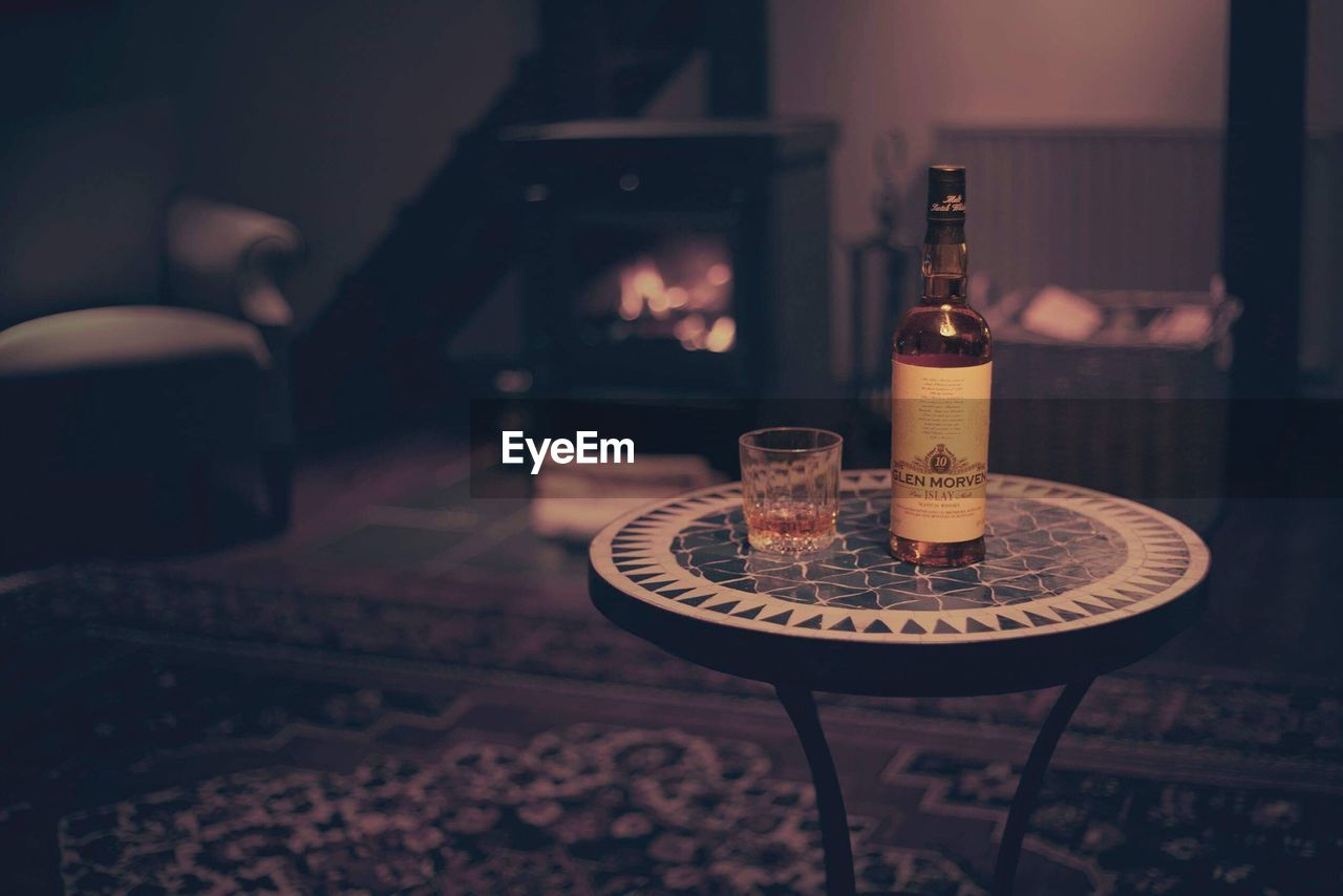 indoors, table, drink, focus on foreground, food and drink, bottle, chair, refreshment, no people, cigarette, absence, ashtray, alcohol, home interior, seat, smoking issues, container, antique, close-up, domestic room