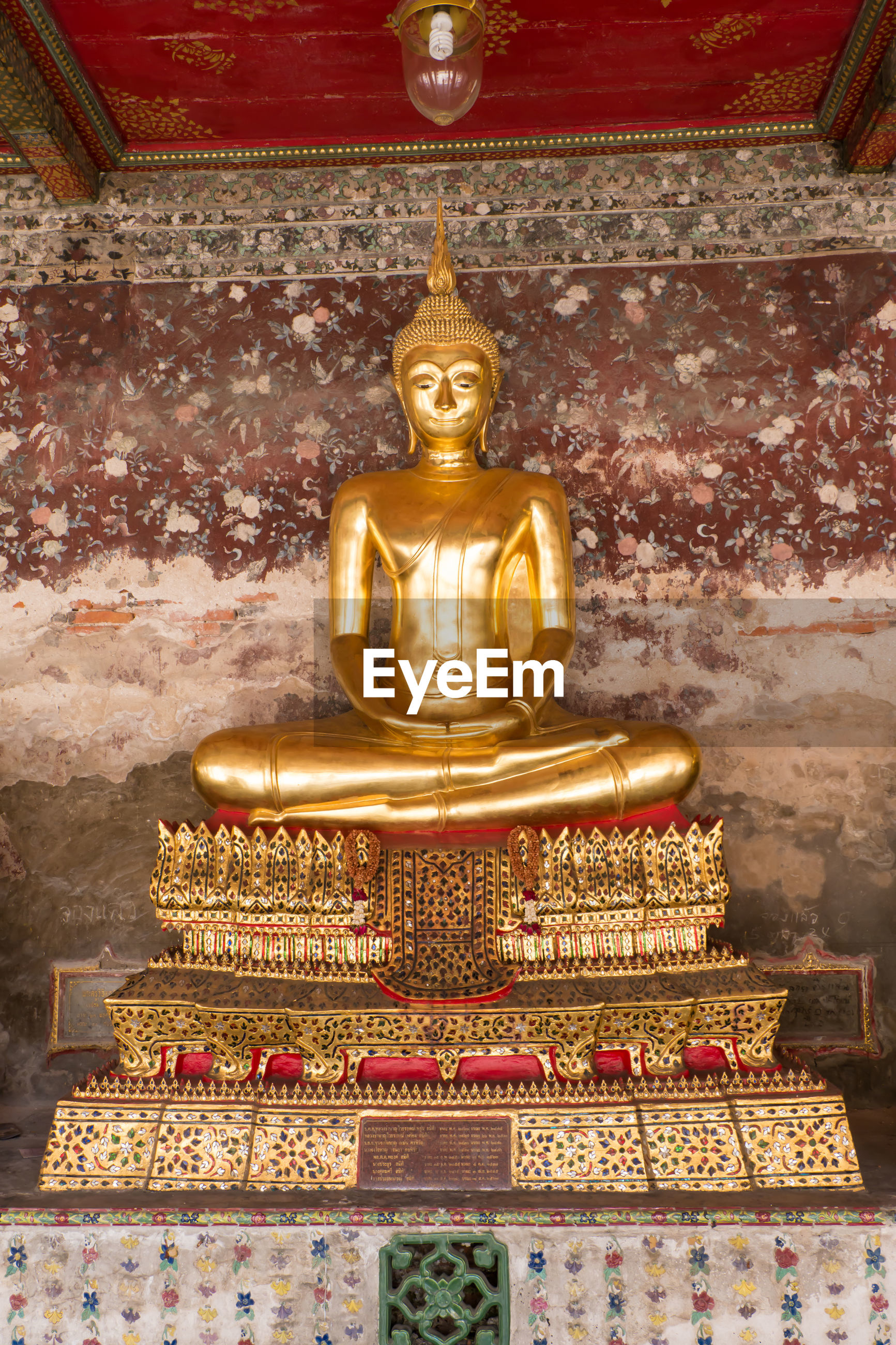 Buddha statue against wall at ancient temple