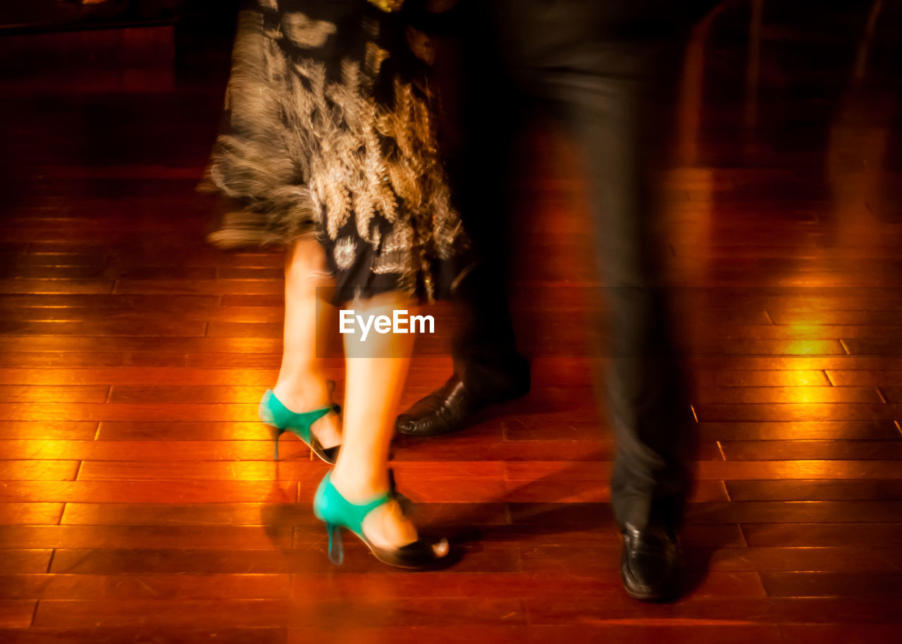 low section, blurred motion, human leg, motion, women, shoe, real people, lifestyles, flooring, indoors, body part, fashion, people, human body part, adult, illuminated, high heels, dancing, leisure activity, wood, human foot, nightlife, human limb, tiled floor