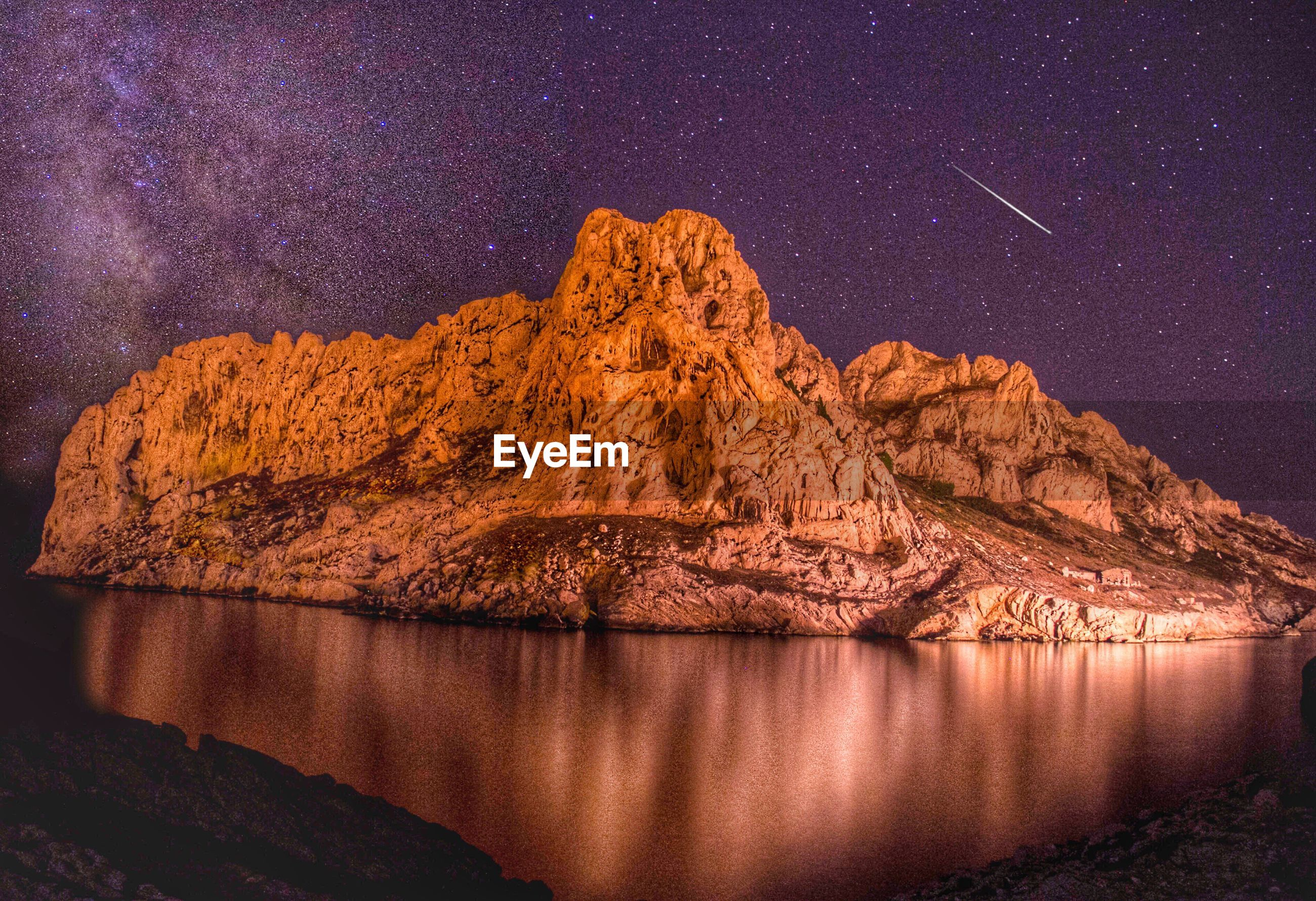 Rocky mountains by river against milky way