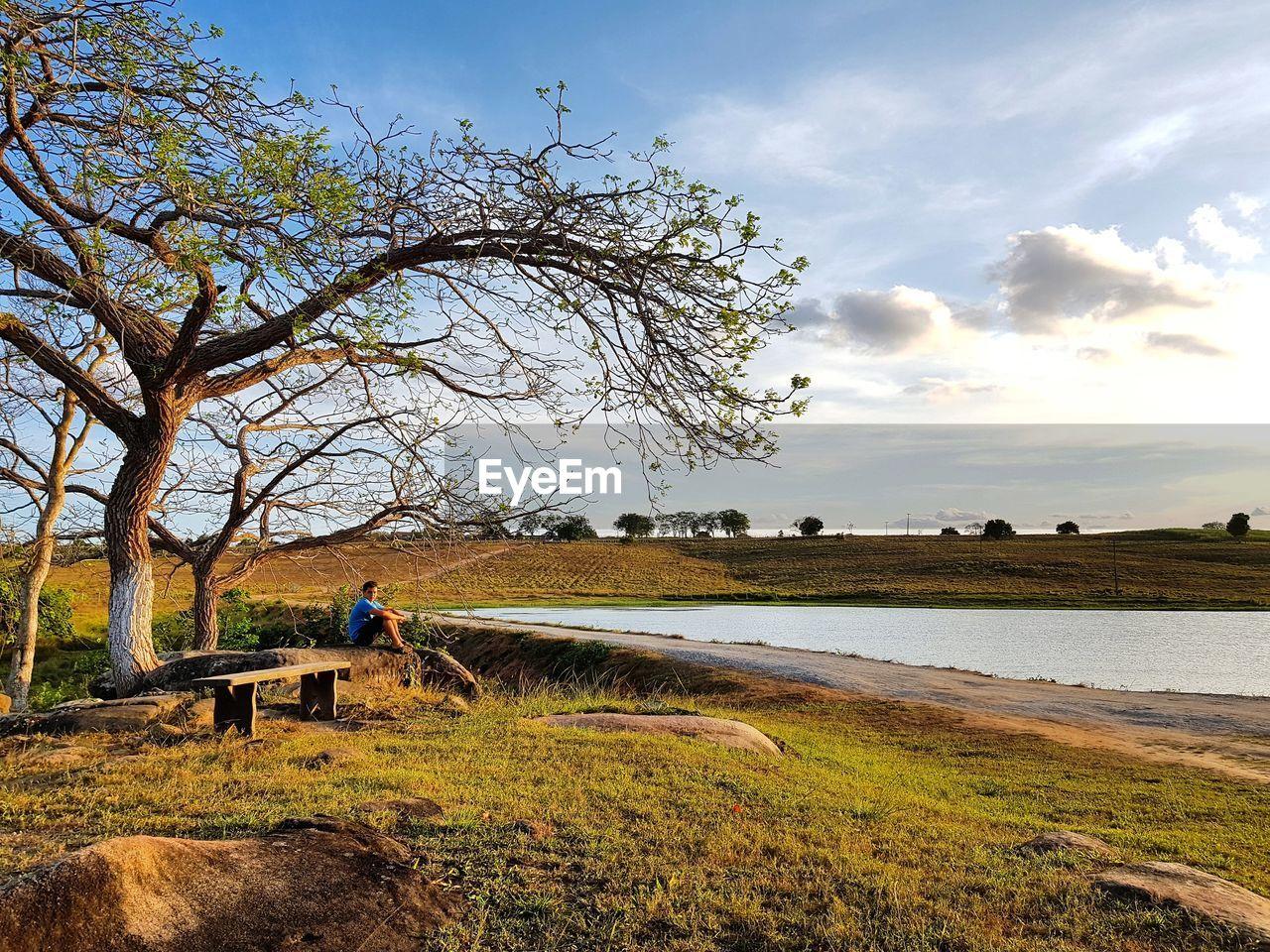 Man Sitting At Lakeshore Against Sky