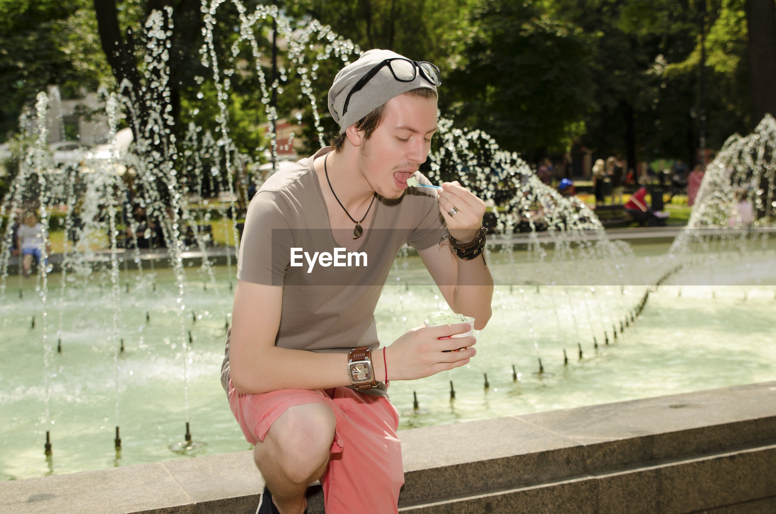 Young man eating ice cream by fountain in park