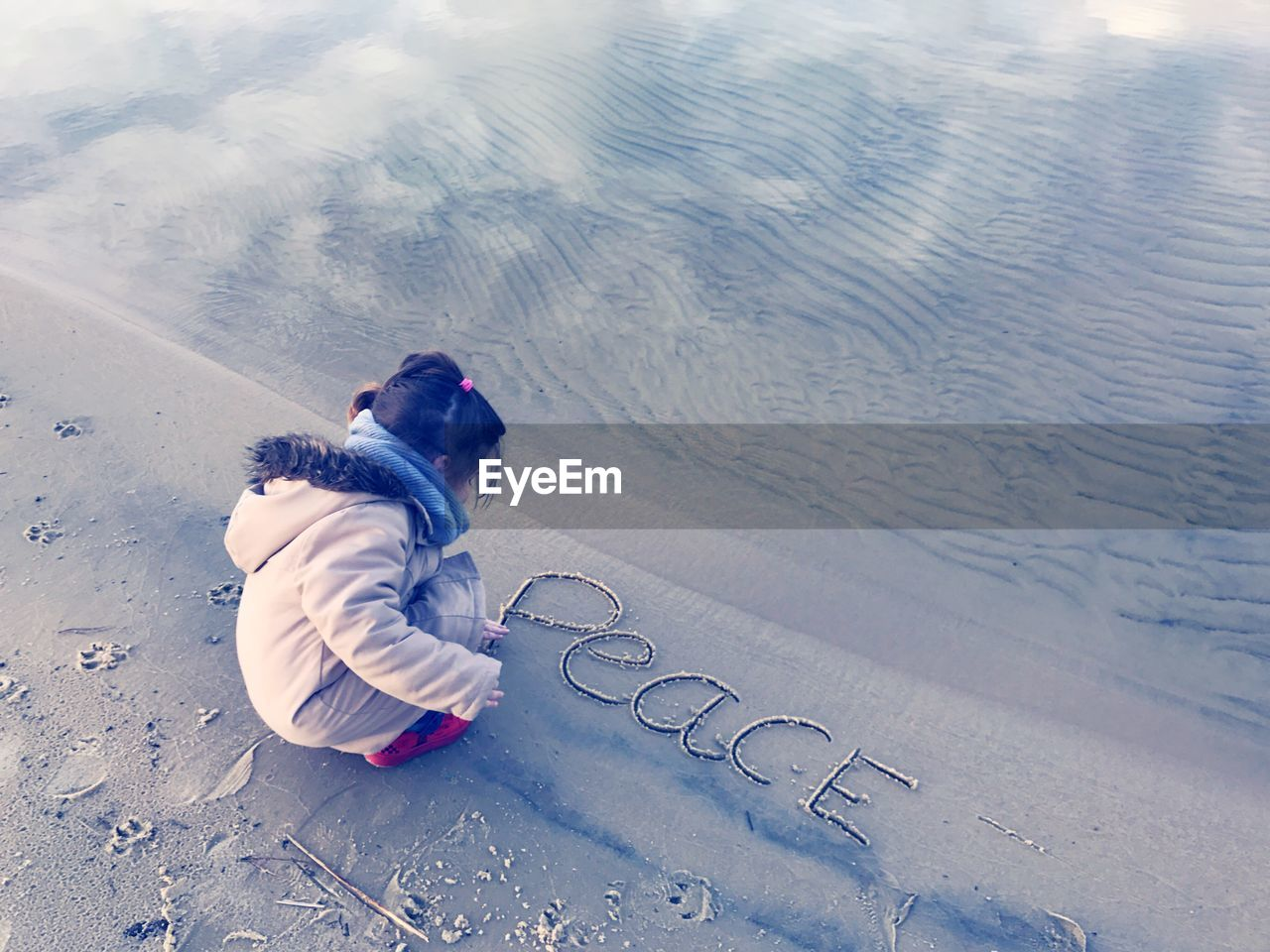 High Angle View Of Girl Writing Peace Text On Shore At Beach