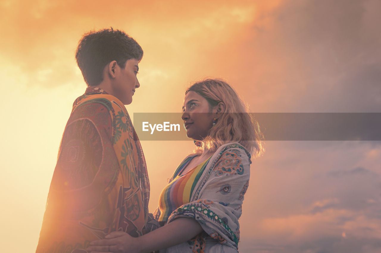 Side view of young same sex couple against sky during sunset