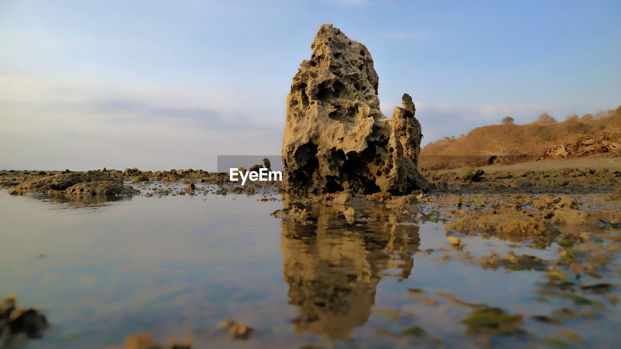 rock - object, nature, tranquility, water, tranquil scene, beauty in nature, sky, waterfront, outdoors, no people, day, scenics