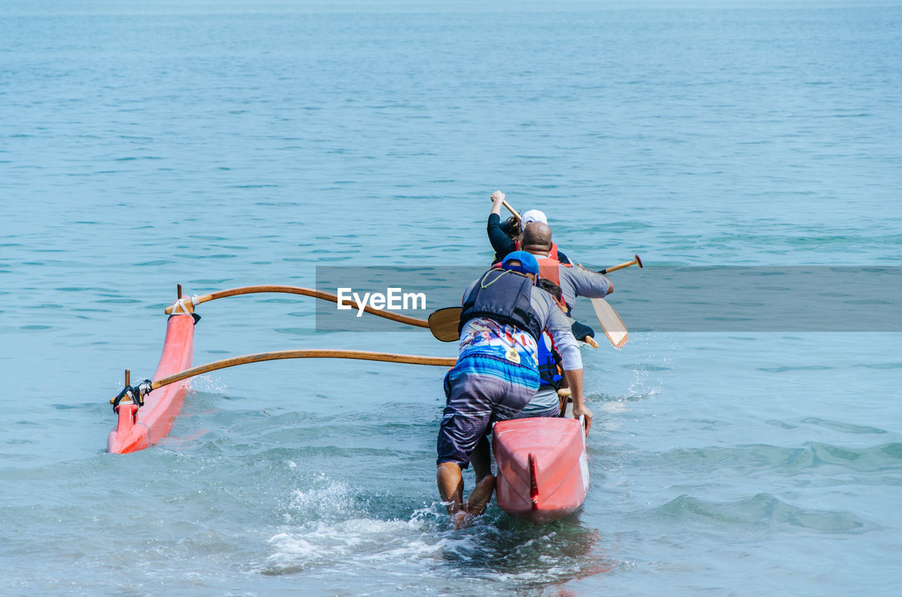 Rear View Of Friends Canoeing On Sea