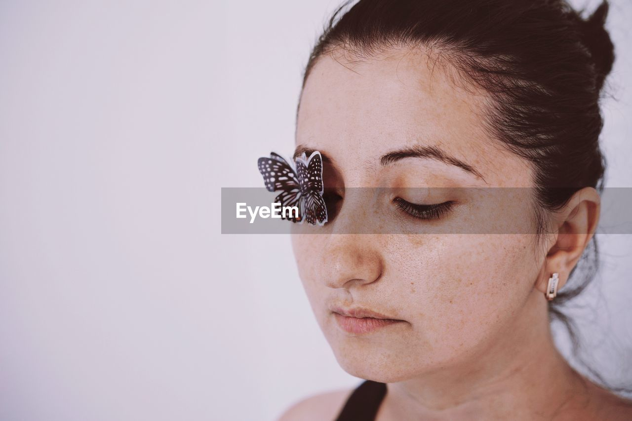 Close-up of young woman with artificial butterfly on eye against white background