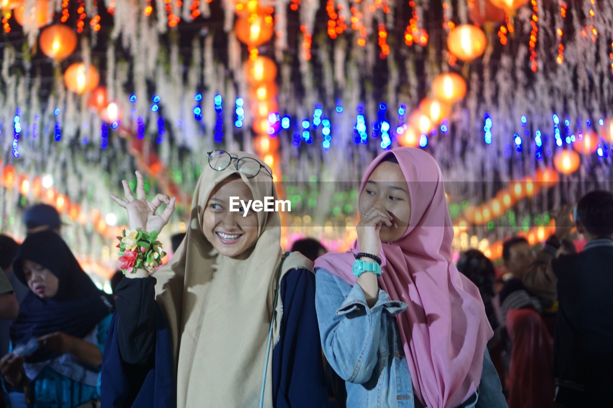 Smiling friends wearing hijab standing against illuminated lights at night