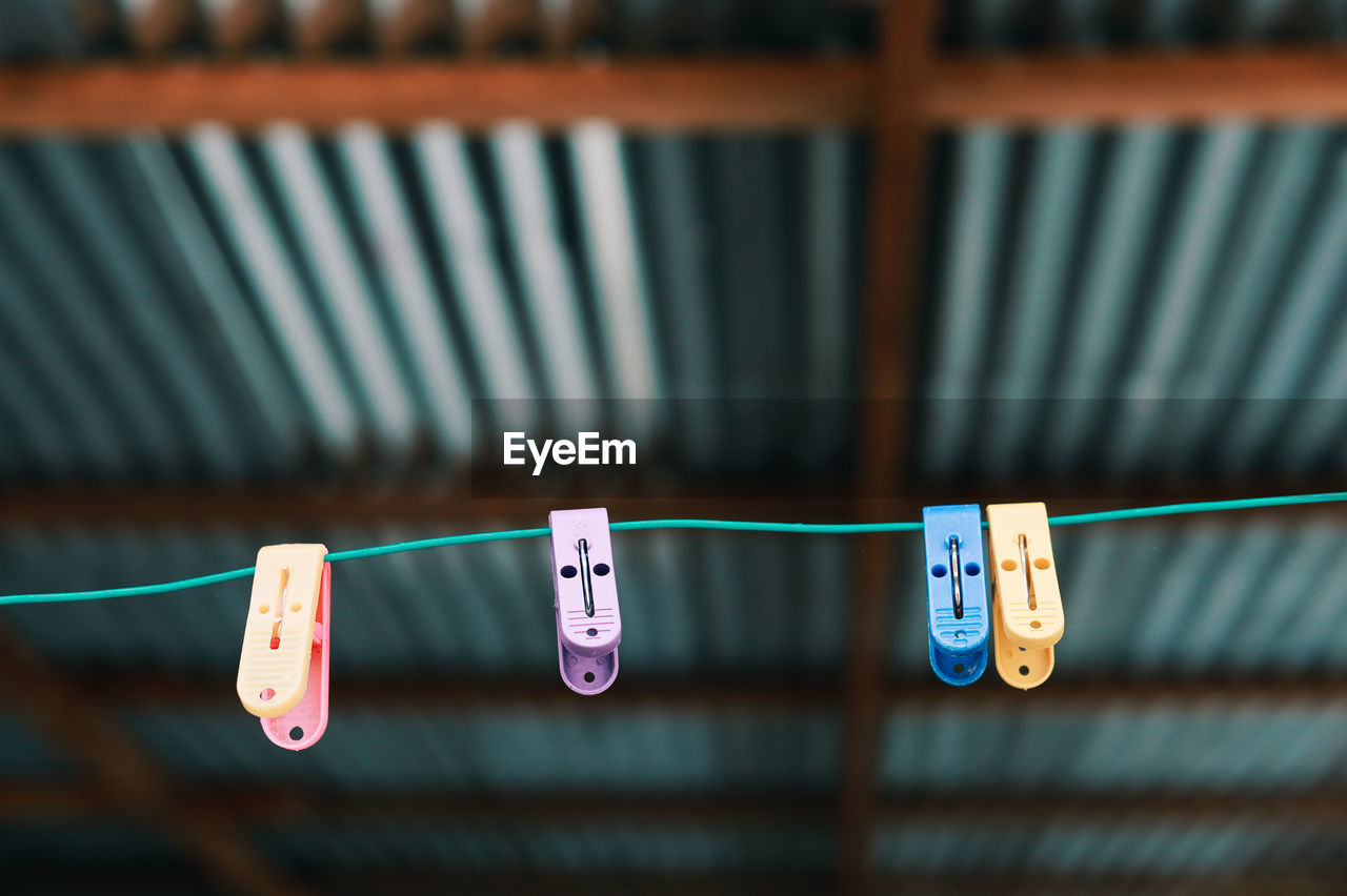 hanging, clothesline, clothespin, focus on foreground, no people, side by side, plastic, close-up, string, clothing, rope, in a row, blue, text, number, communication, group of objects, still life, day, indoors