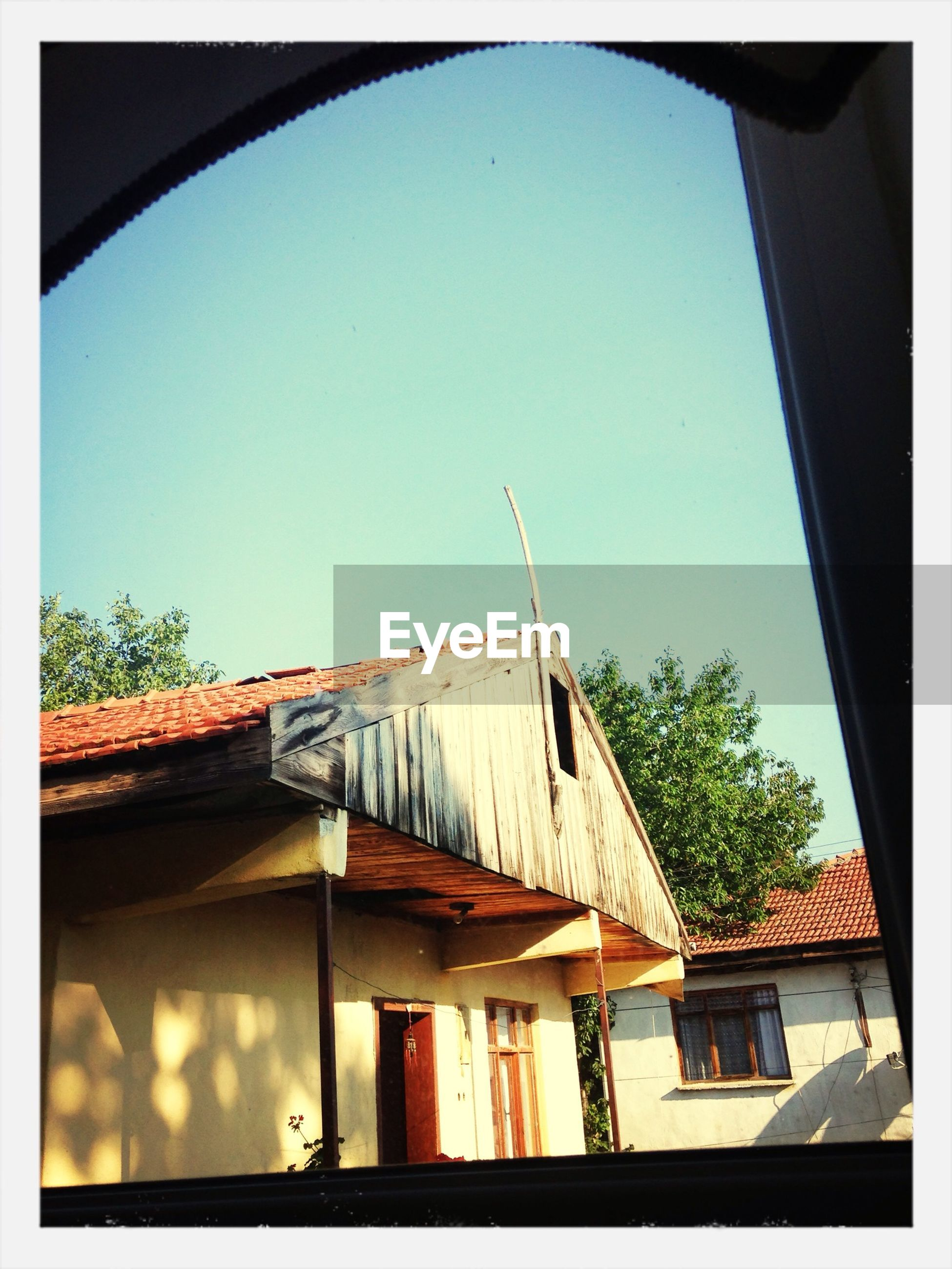 architecture, built structure, building exterior, clear sky, transfer print, house, low angle view, residential structure, window, auto post production filter, residential building, roof, blue, balcony, day, tree, sky, copy space, sunlight, building