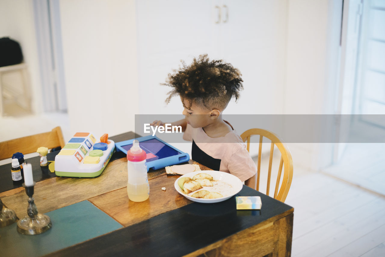 BOY HOLDING FOOD ON TABLE