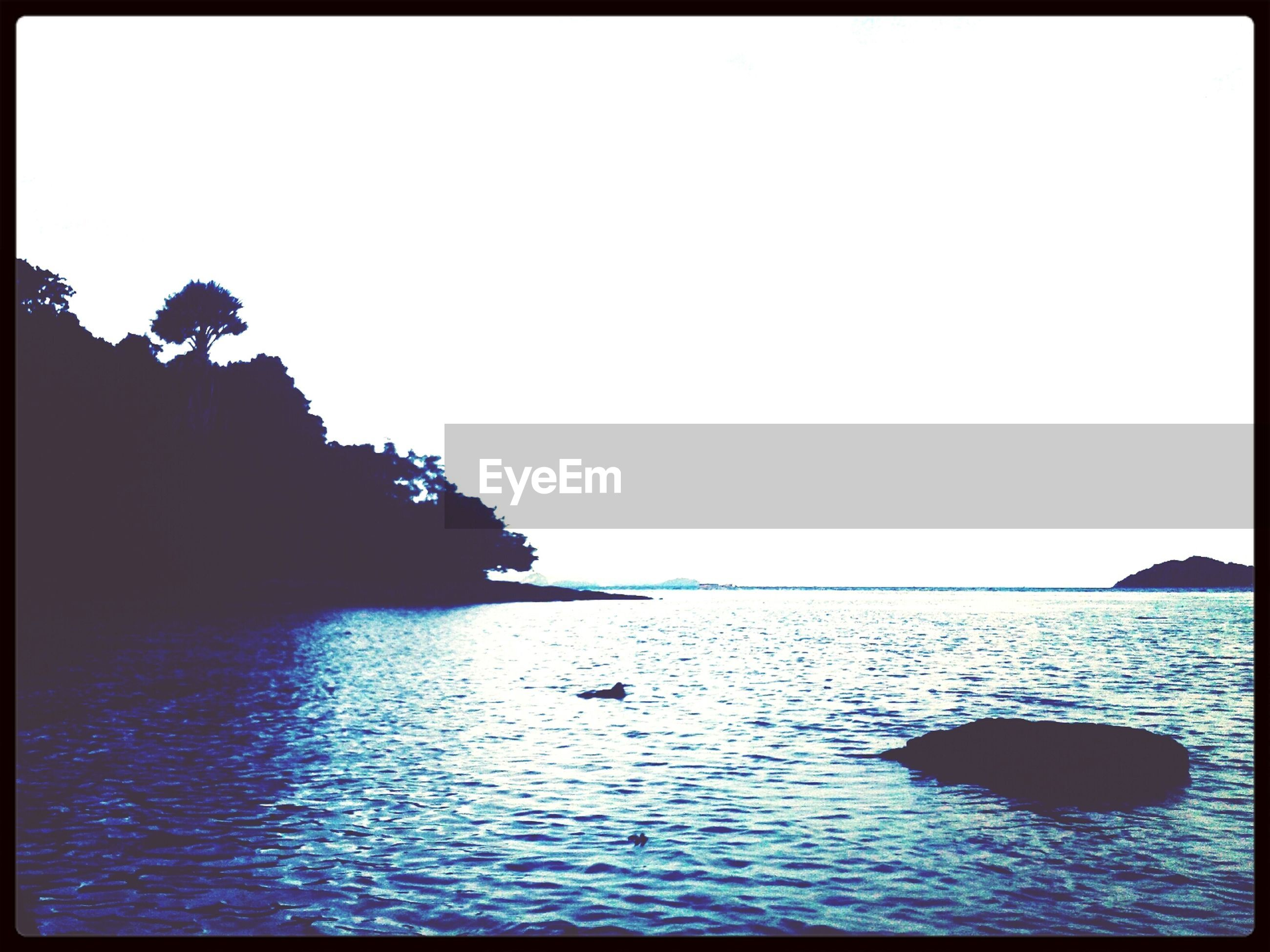 water, clear sky, transfer print, copy space, tranquil scene, tranquility, sea, waterfront, scenics, beauty in nature, auto post production filter, nature, silhouette, rippled, idyllic, calm, outdoors, horizon over water, no people, rock - object