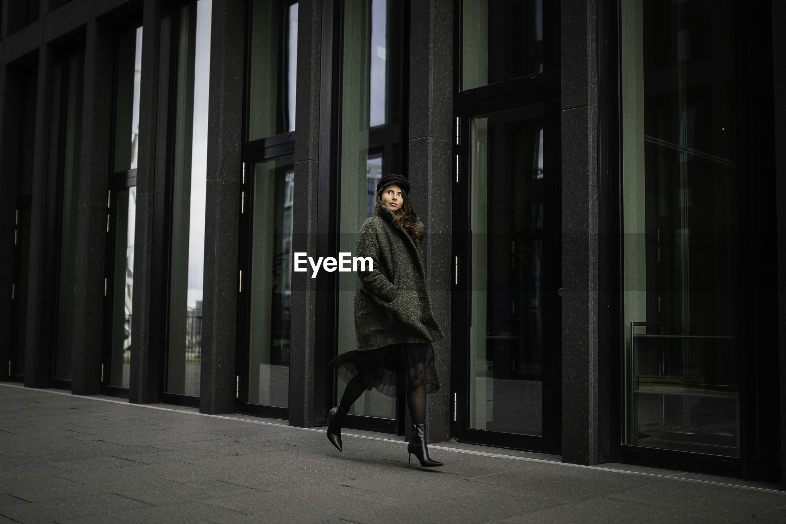 Full length of woman walking by building