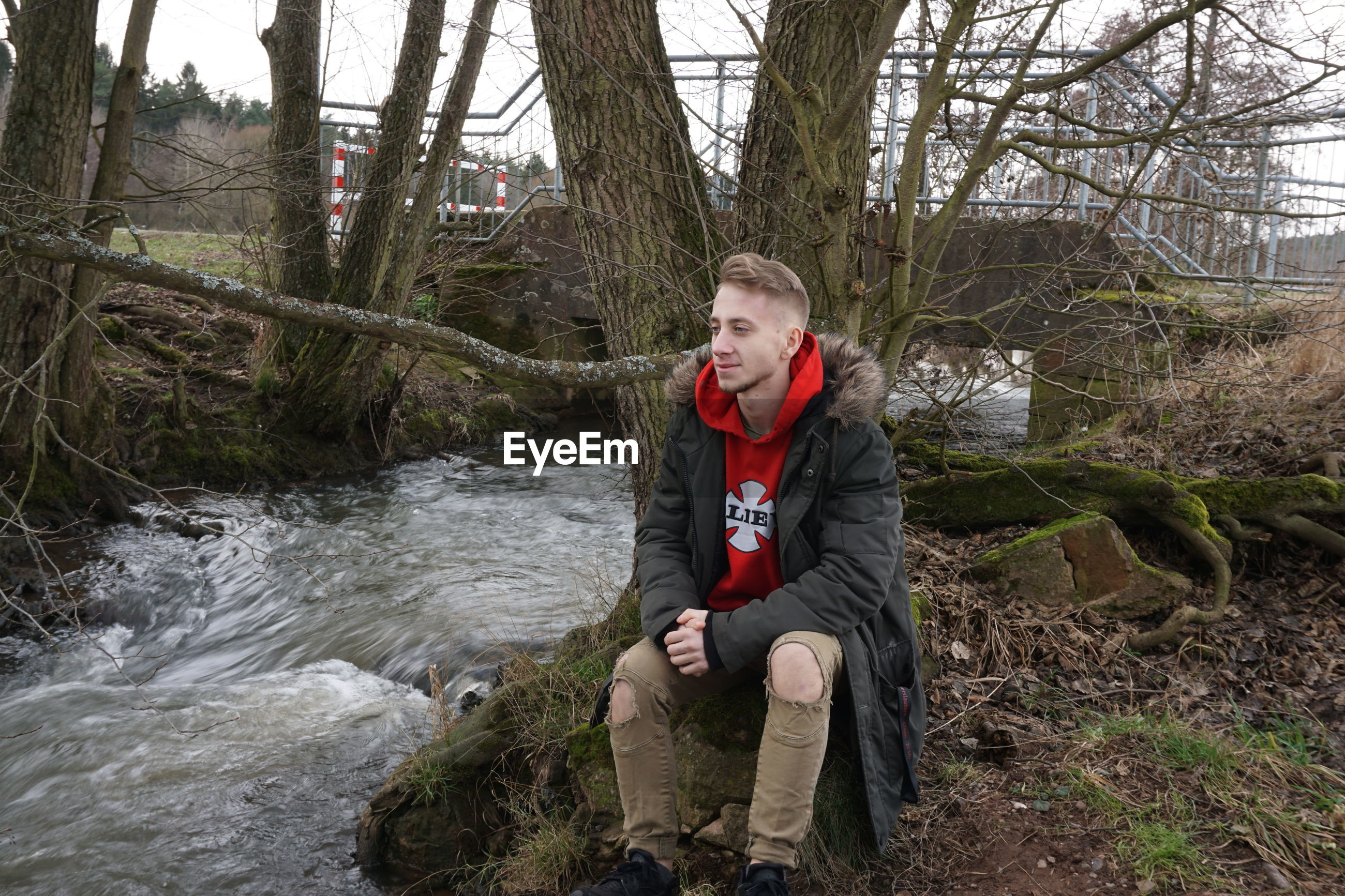 Side view of man sitting by river in forest