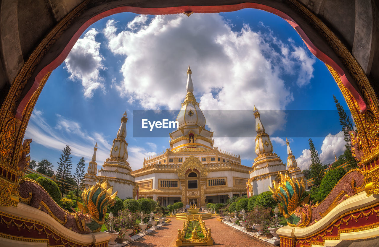 religion, spirituality, place of worship, architecture, sky, built structure, building exterior, cloud - sky, sculpture, day, travel destinations, statue, no people, outdoors, golden color, nature, fish-eye lens, tree