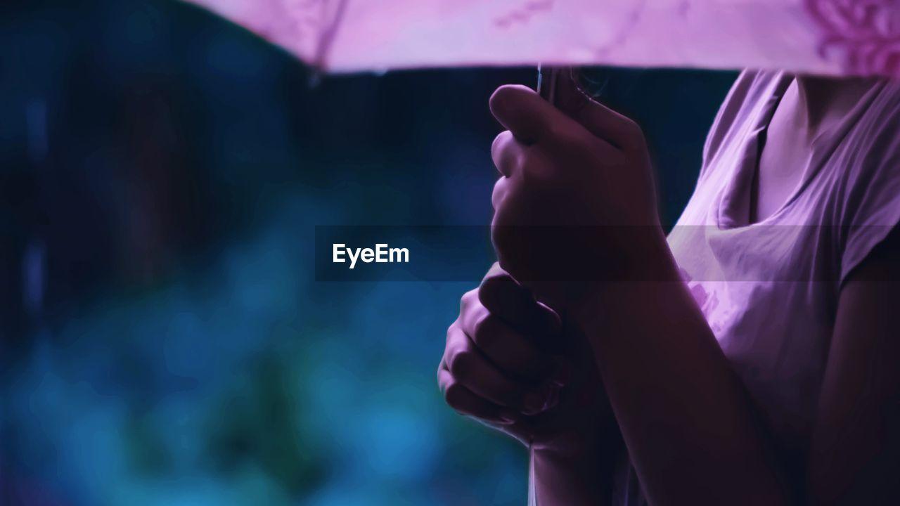 Cropped Image Of Woman Holding Umbrella During Rainy Season