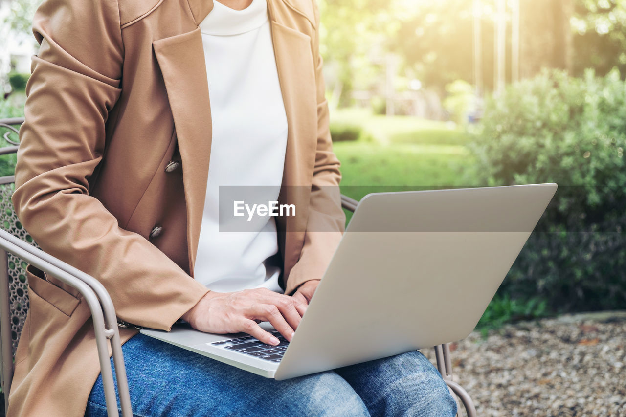 Midsection Of Woman Using Laptop While Sitting On Chair