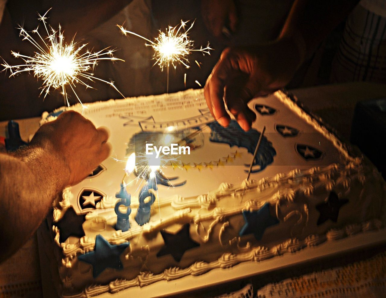 human hand, celebration, human body part, flame, sparkler, burning, illuminated, glowing, real people, candle, indoors, birthday, motion, table, cake, birthday cake, men, sweet food, heat - temperature, holding, birthday candles, close-up, night, togetherness, people