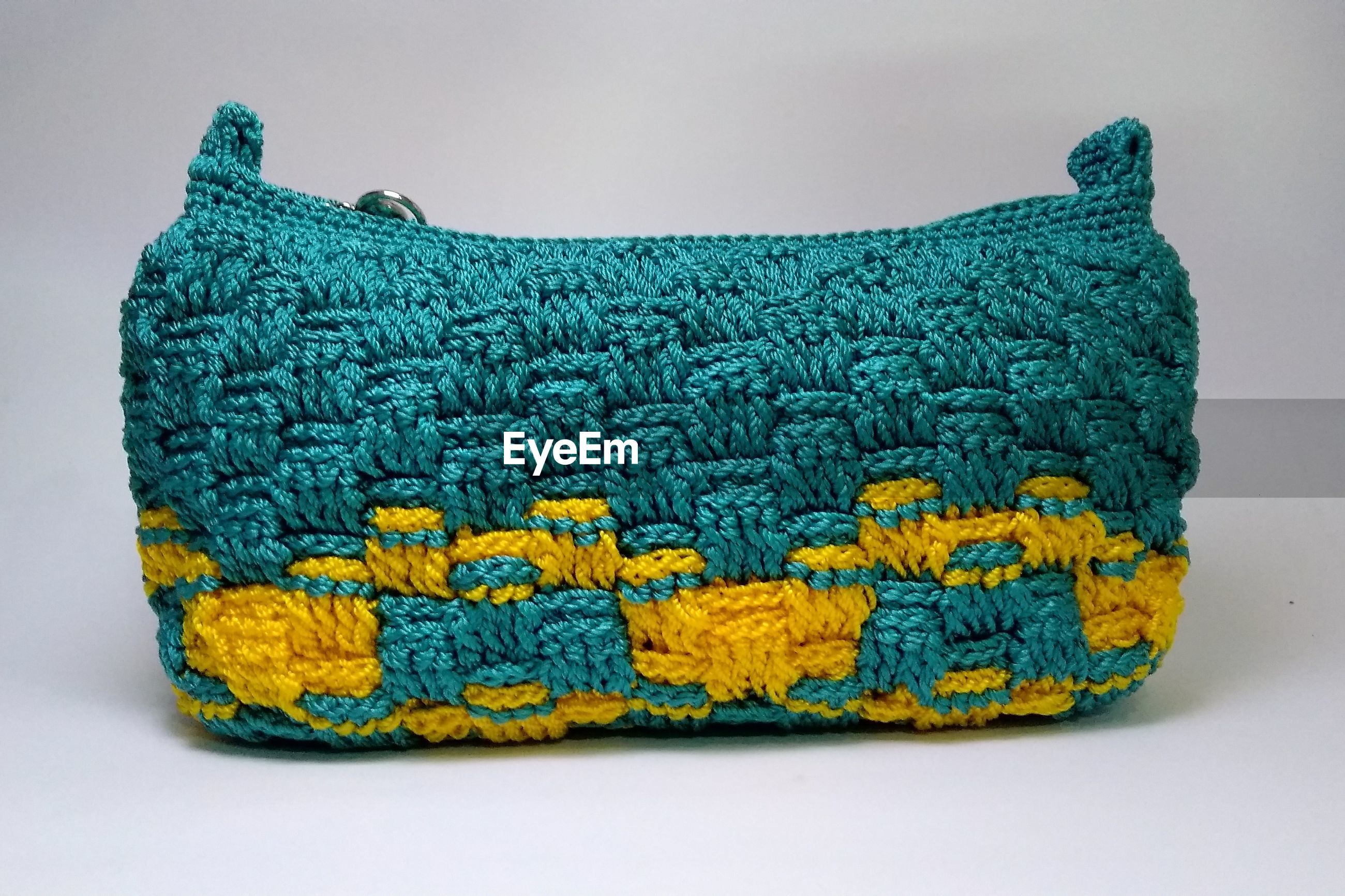 Close-up of knitted bag against white background