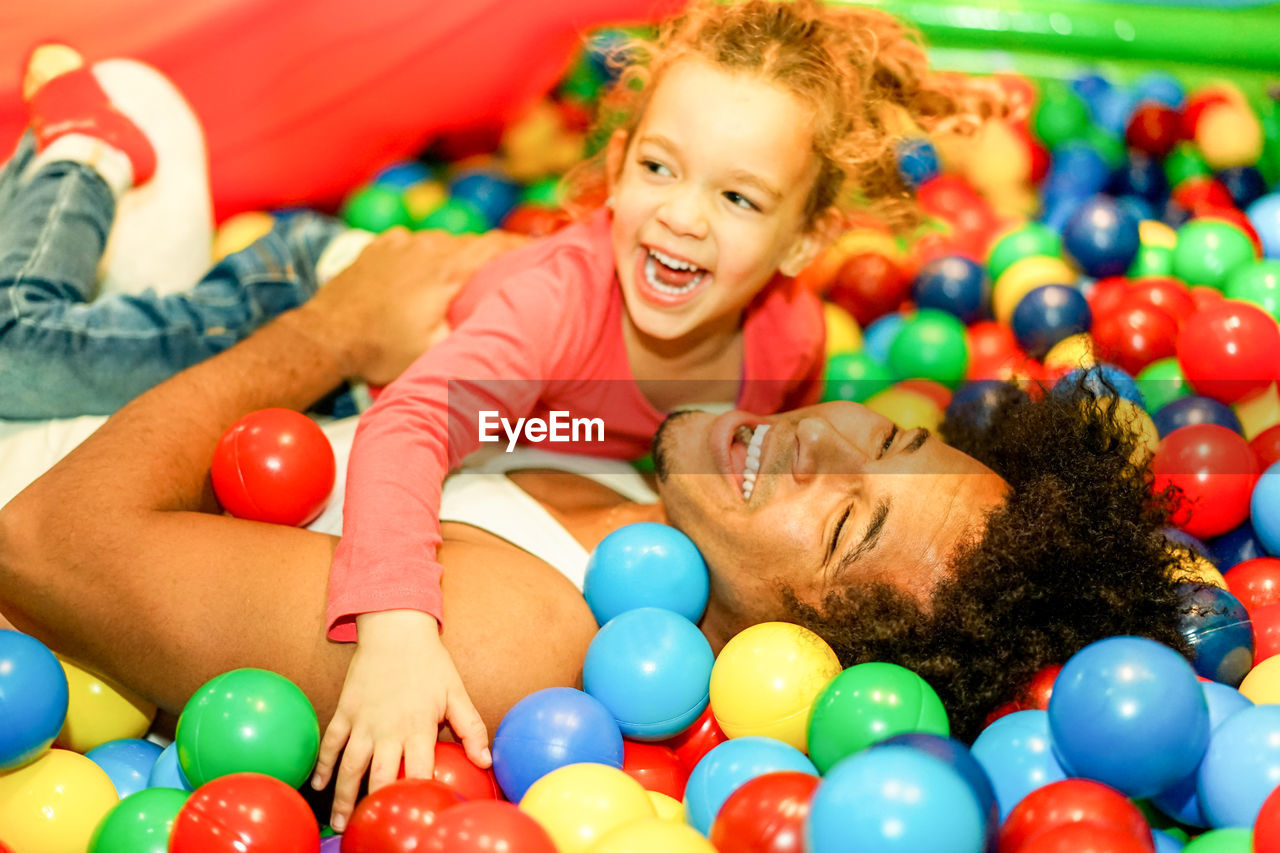 Happy Father And Daughter Playing With Multi Colored Balls In Pool