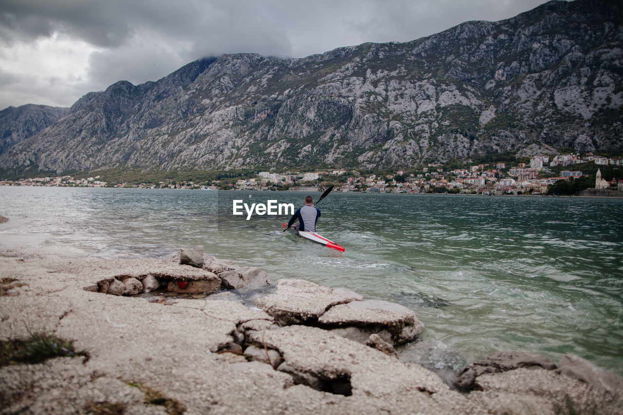 Man Kayaking In River Against Mountains