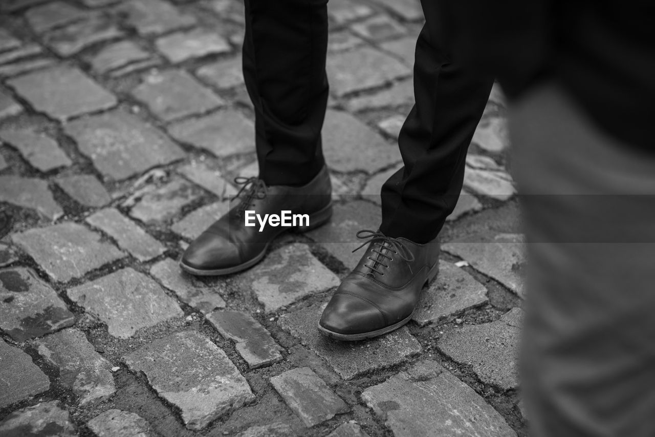shoe, low section, human leg, human body part, body part, real people, footpath, two people, street, city, men, day, people, cobblestone, standing, lifestyles, outdoors, stone, selective focus, togetherness, human foot, paving stone, human limb, leather