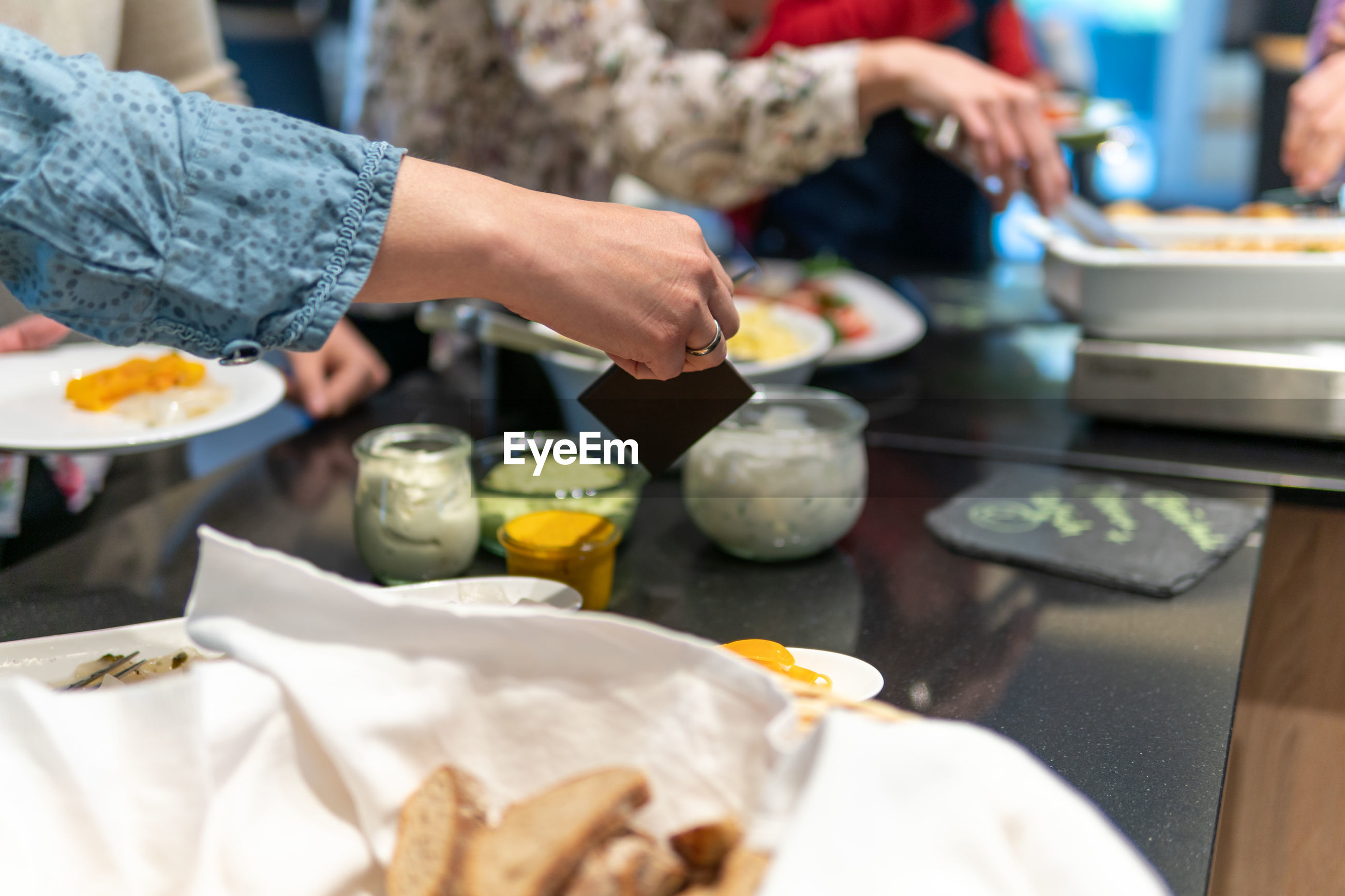 MIDSECTION OF WOMAN HOLDING FOOD AT TABLE IN KITCHEN