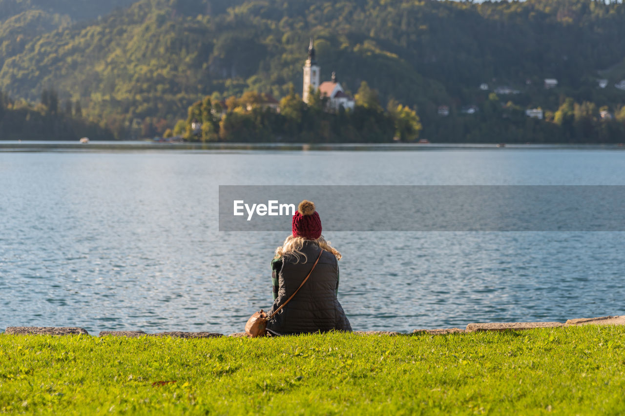water, real people, one person, lifestyles, nature, lake, leisure activity, beauty in nature, plant, women, rear view, day, focus on foreground, sitting, tranquility, adult, scenics - nature, tranquil scene, outdoors, hairstyle, looking at view