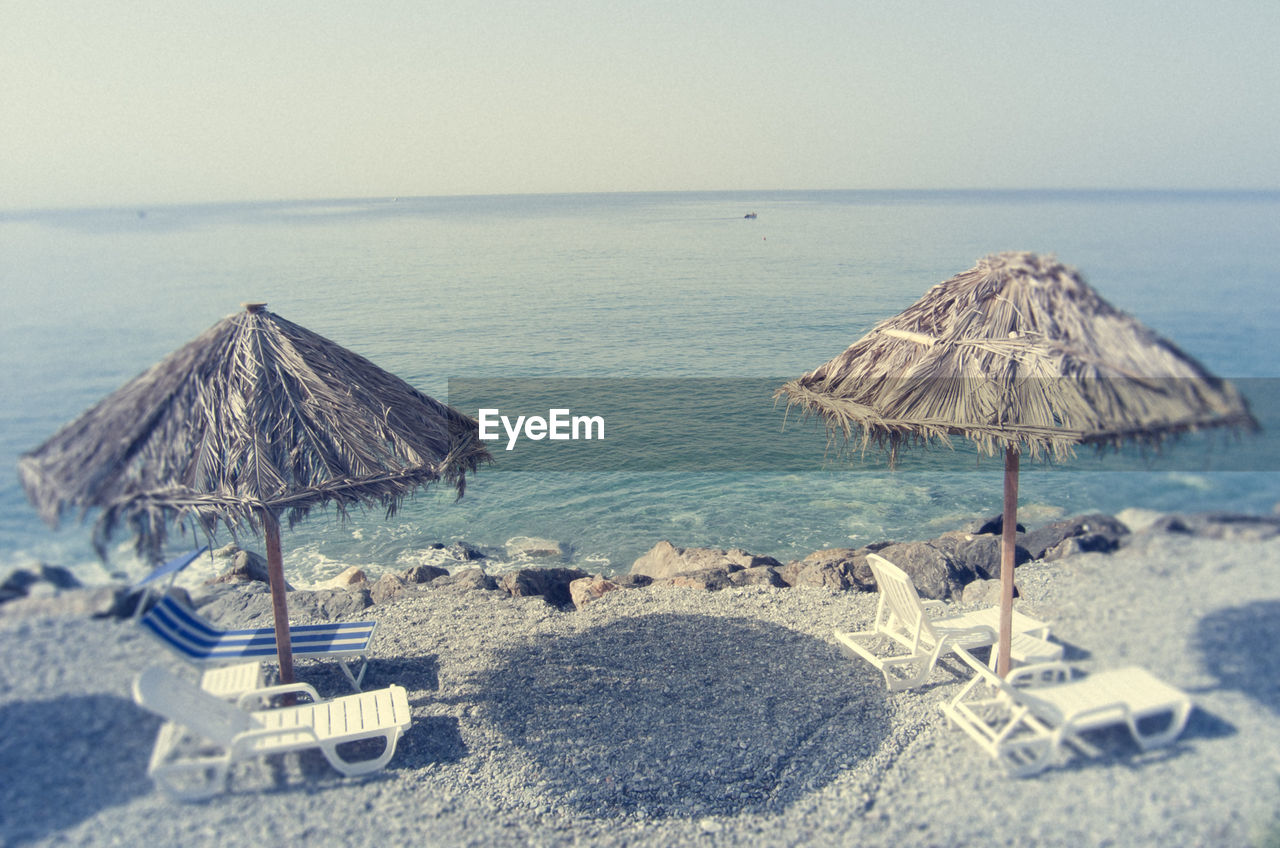 sea, horizon over water, beach, thatched roof, water, scenics, beauty in nature, tranquil scene, nature, no people, tranquility, clear sky, day, outdoors, vacations, sand, sky