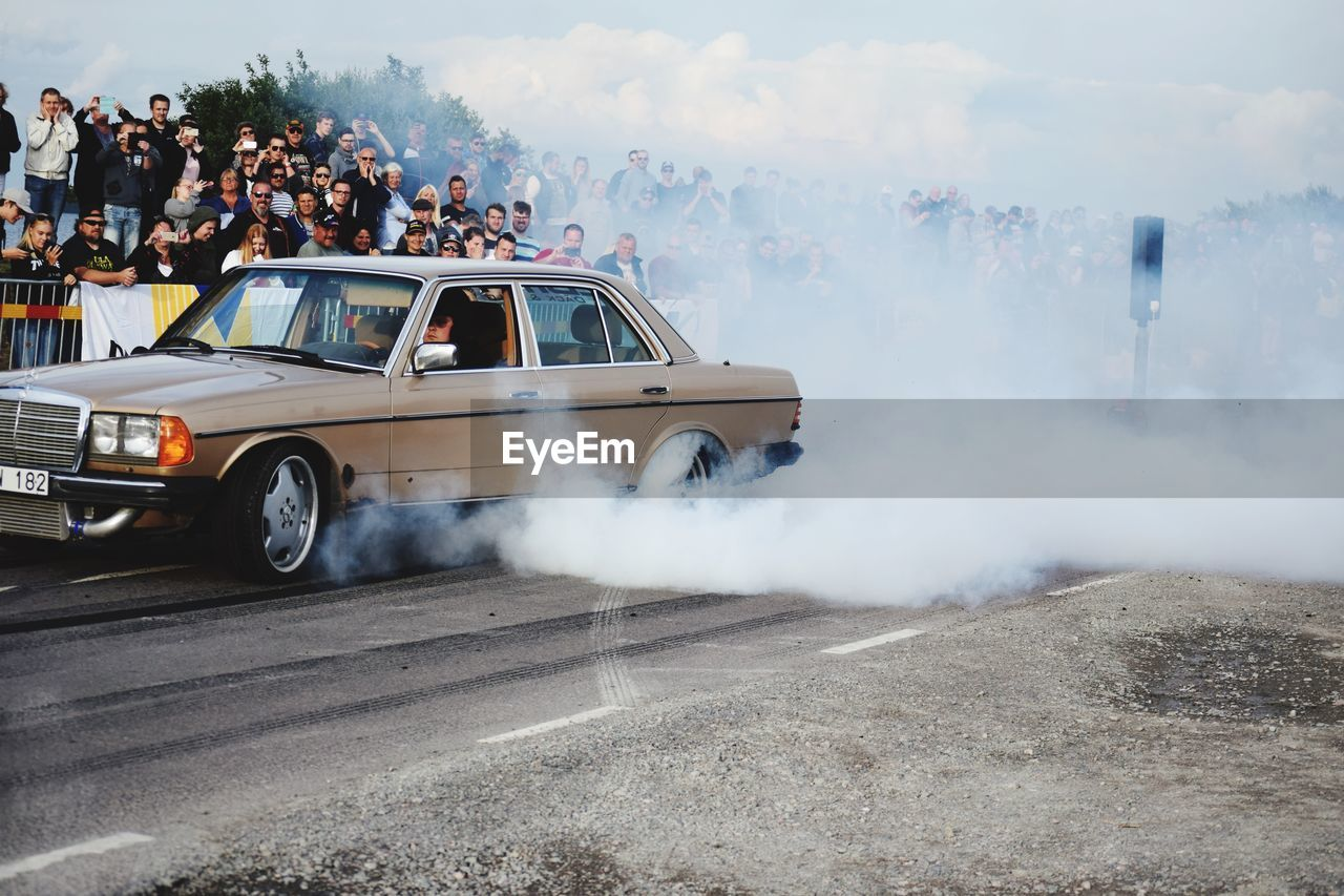transportation, mode of transportation, smoke - physical structure, car, motor vehicle, group of people, day, crowd, real people, land vehicle, road, motion, large group of people, men, nature, city, women, burning, sign, pollution, explosive
