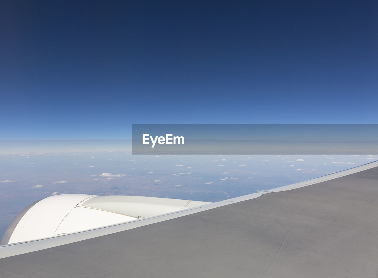 Cropped Image Of Airplane Flying Over Sea