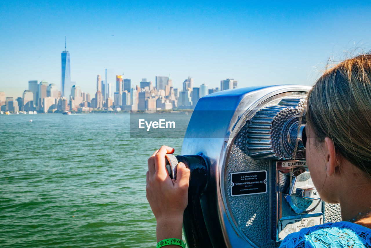 Girl looking through coin-operated binoculars against clear sky