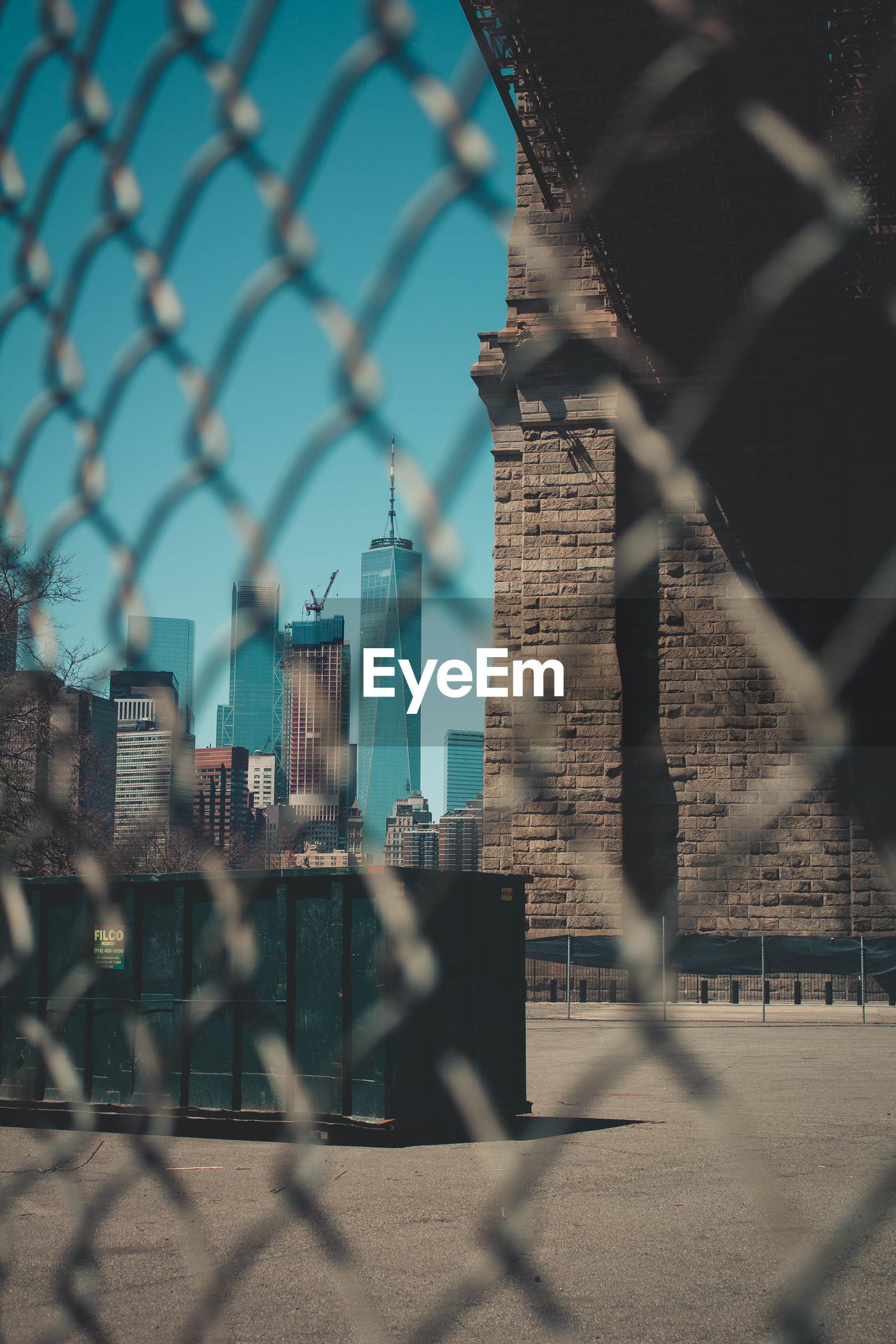 Cityscape seen through chainlink fence against sky