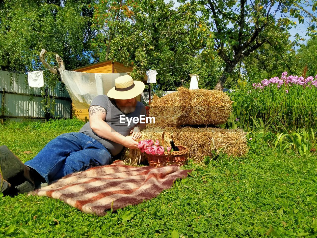 MIDSECTION OF WOMAN SITTING BY POTTED PLANT IN FIELD