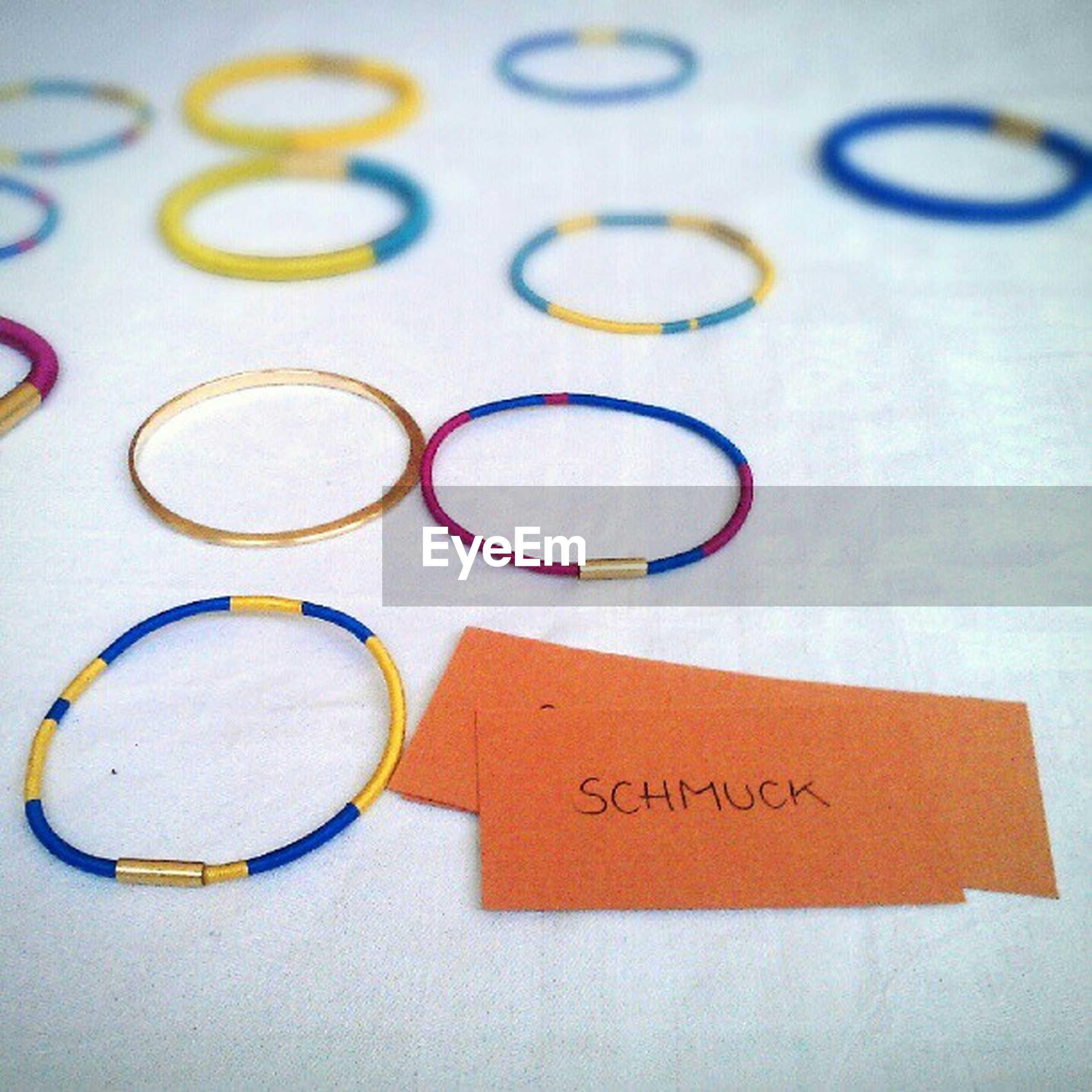 indoors, text, communication, close-up, western script, still life, table, high angle view, paper, studio shot, number, circle, white background, variation, creativity, multi colored, no people, selective focus, ideas, capital letter