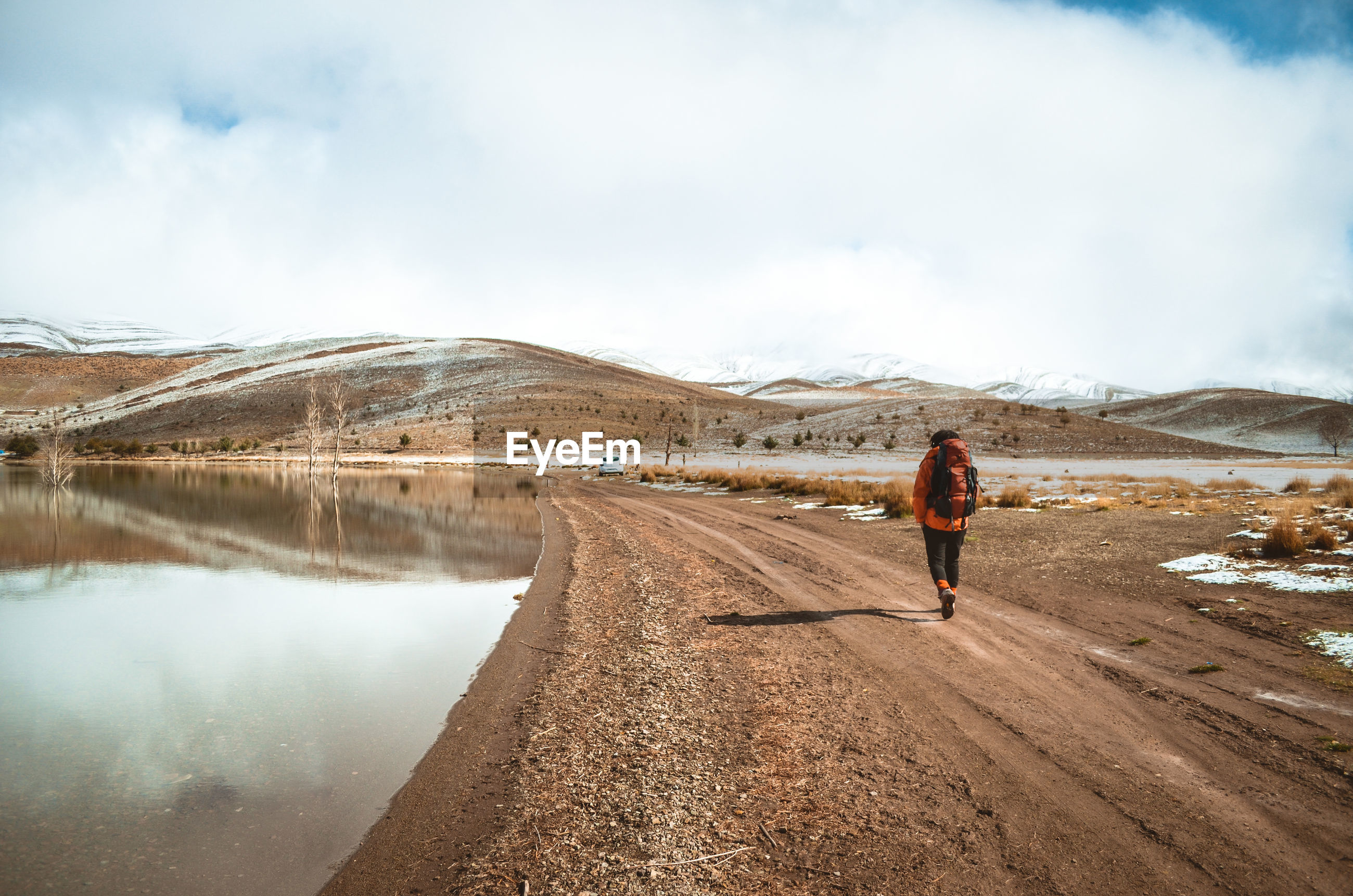 Rear view of man walking on dirt road against cloudy sky