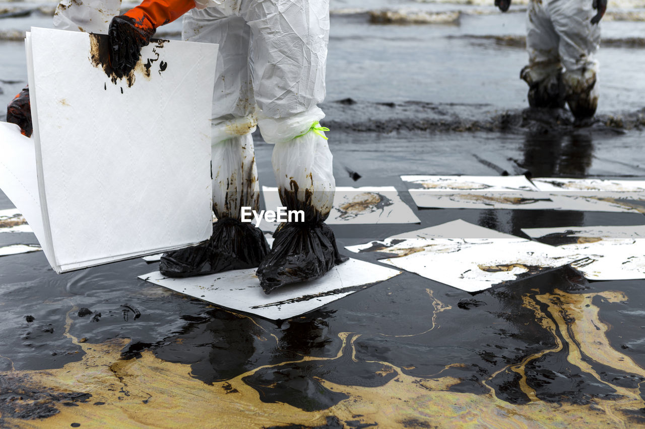 Low section of volunteers holding cardboards while standing in oil at beach