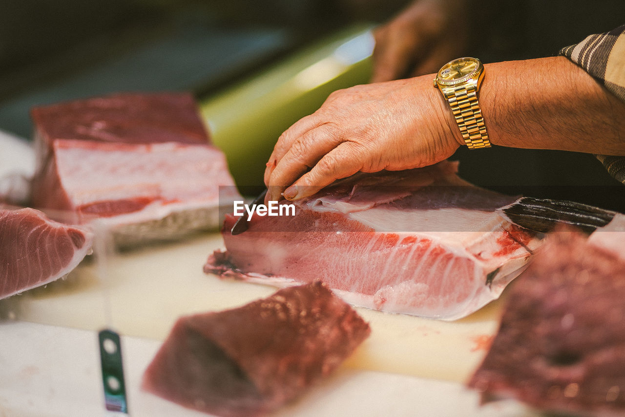 Close-Up Of Hands Cutting Meat