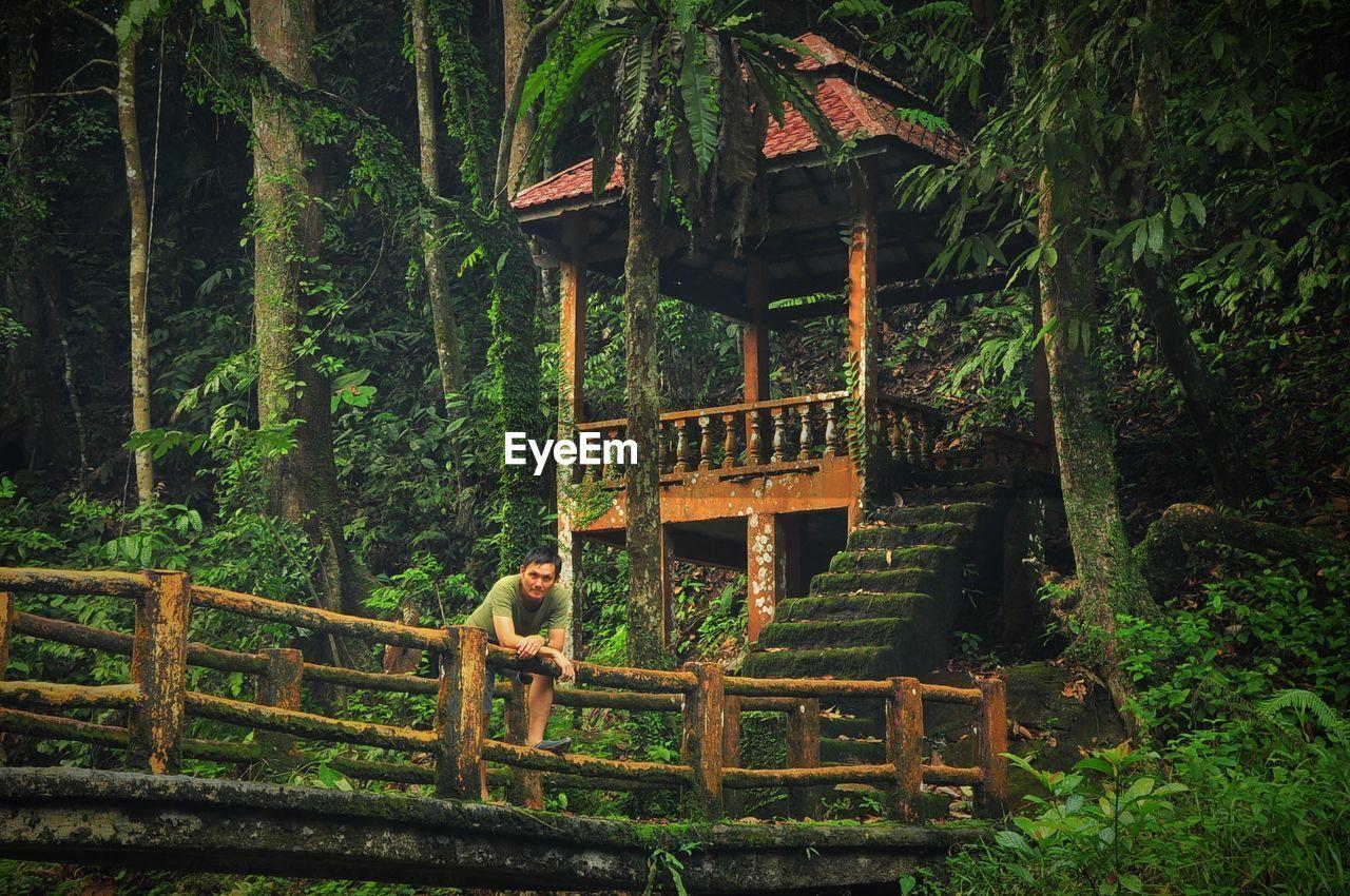 Man Standing On Footbridge By Gazebo Amidst Trees In Forest