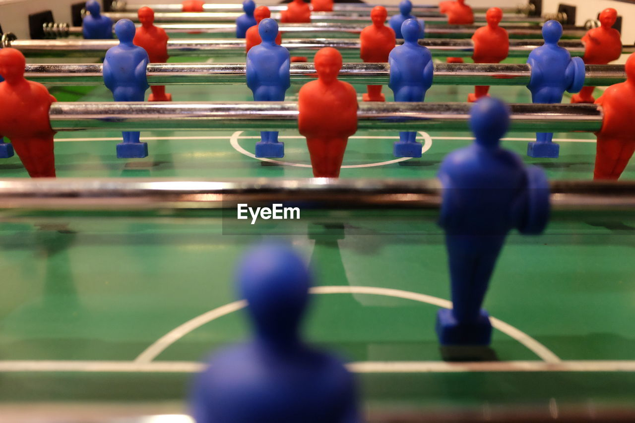 sport, leisure games, competition, leisure activity, team sport, relaxation, soccer, representation, competitive sport, teamwork, cooperation, figurine, human representation, blue, male likeness, strategy, challenge, in a row, people, group of people, swimming pool