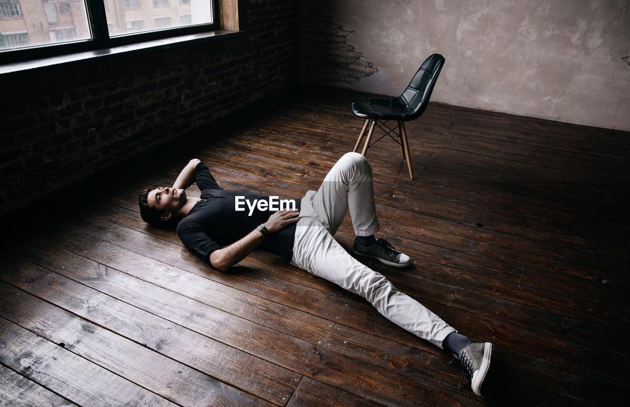 Handsome man lying on hardwood floor at film studio