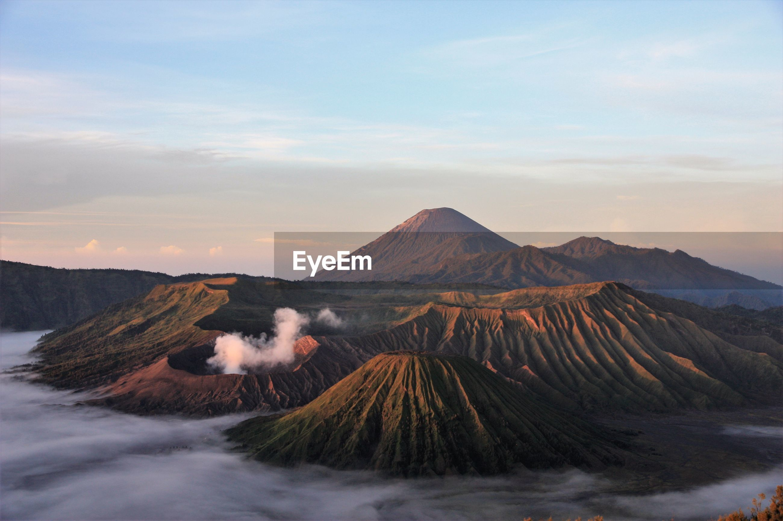 Scenic view of mountain range against sky in foggy weather