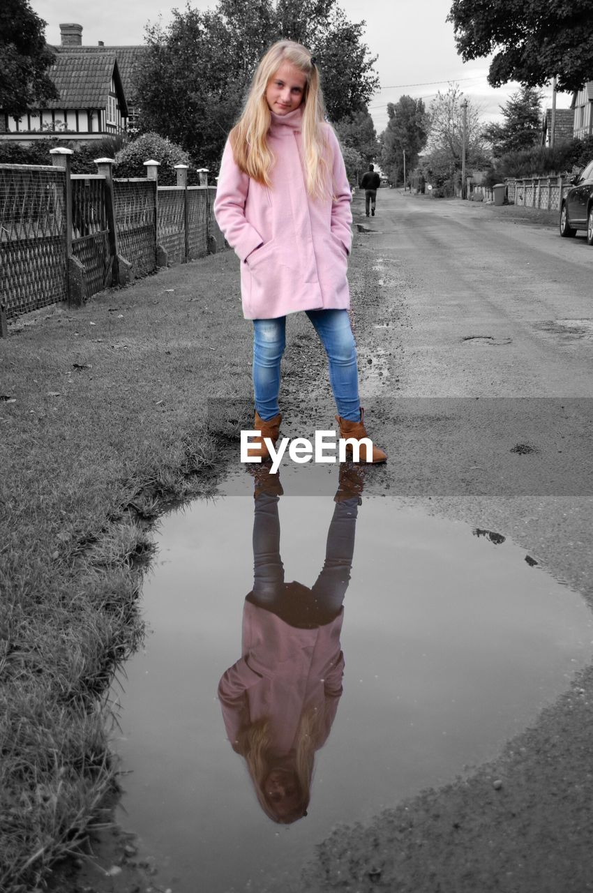 Portrait of girl wearing pink raincoat standing by puddle on street in city