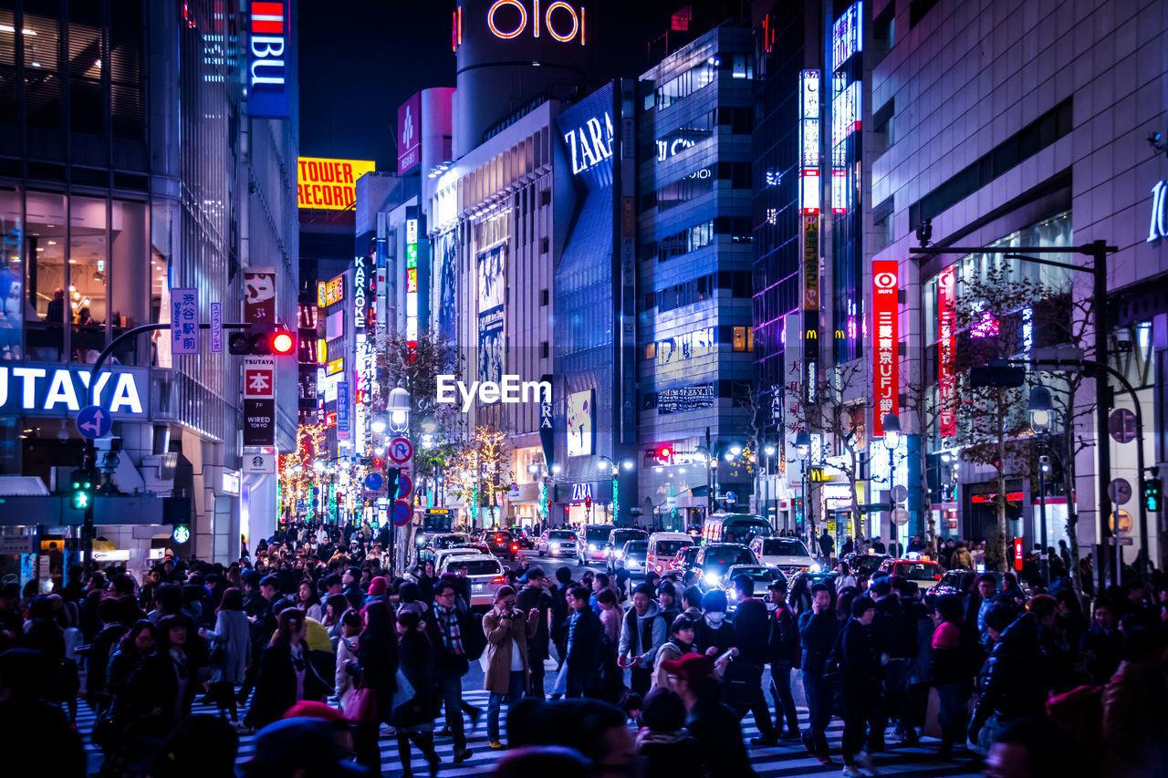Crowd On Street Amidst Illuminated Buildings At Night