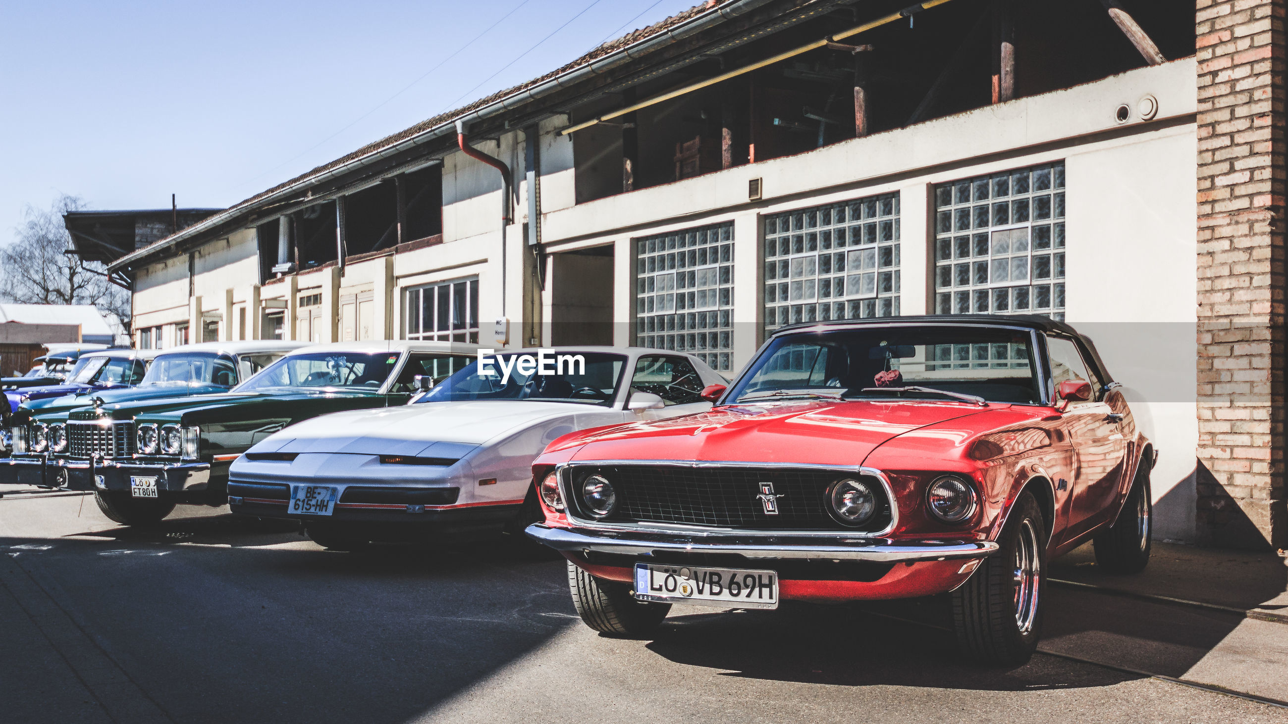 mode of transportation, car, motor vehicle, transportation, land vehicle, architecture, city, building exterior, built structure, street, stationary, day, sunlight, building, retro styled, vintage car, no people, road, in a row, outdoors, luxury