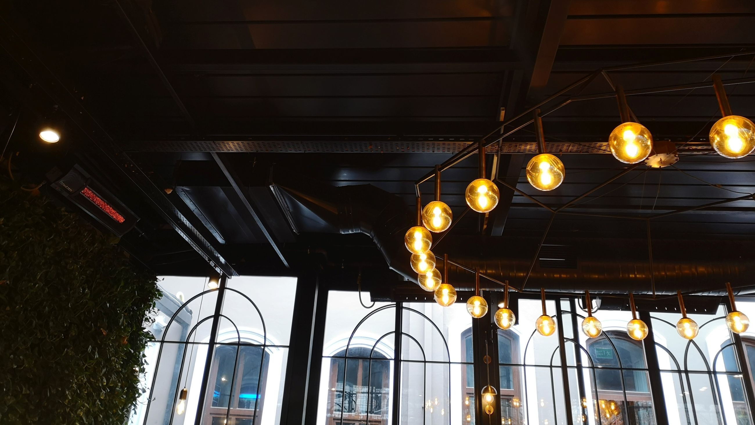 LOW ANGLE VIEW OF ILLUMINATED PENDANT LIGHT HANGING ON CEILING OF BUILDING