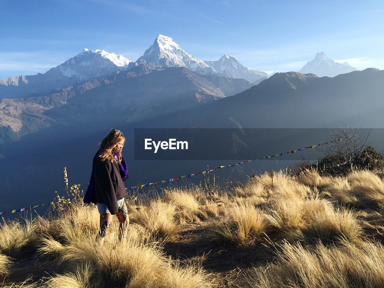 Woman Hiking On Grassy Field Against Mountains