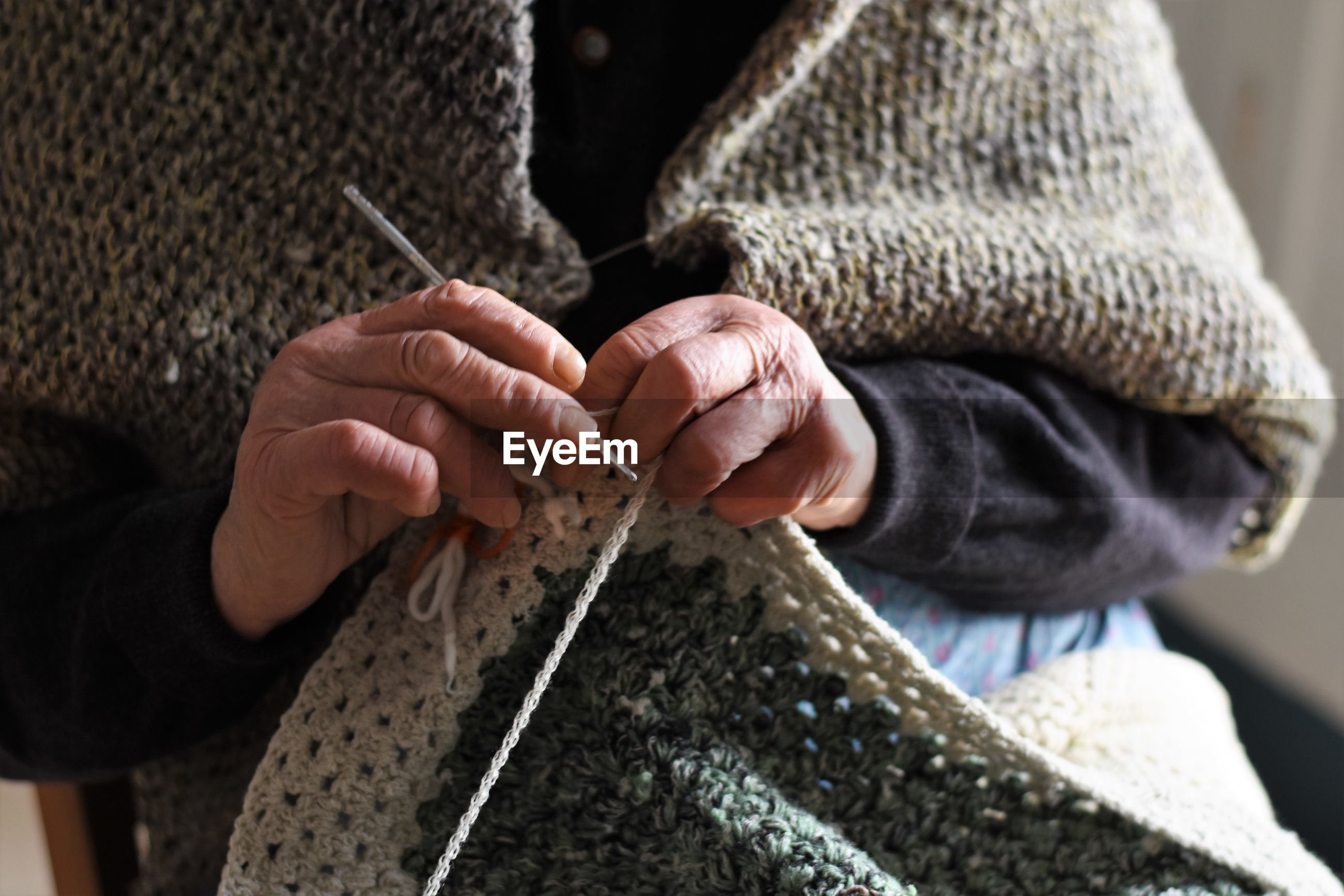 Midsection of woman knitting